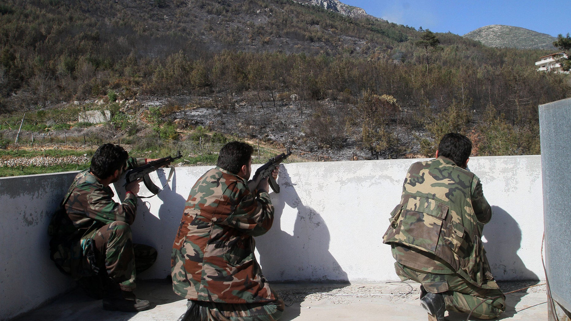 March 27, 2014: In this photo Syrian government soldiers take position during clashes with rebels in Misherfeh town in the province of Latakia, Syria.