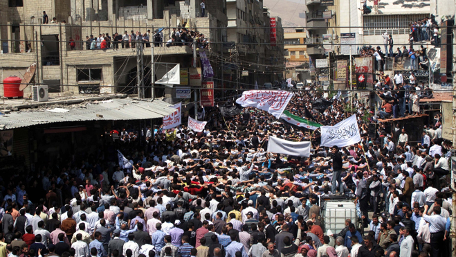 April 20, 2012: Syrians wave Islamic and revolutionary flags at a large protest in Douma, a suburb of Damascus, Syria.