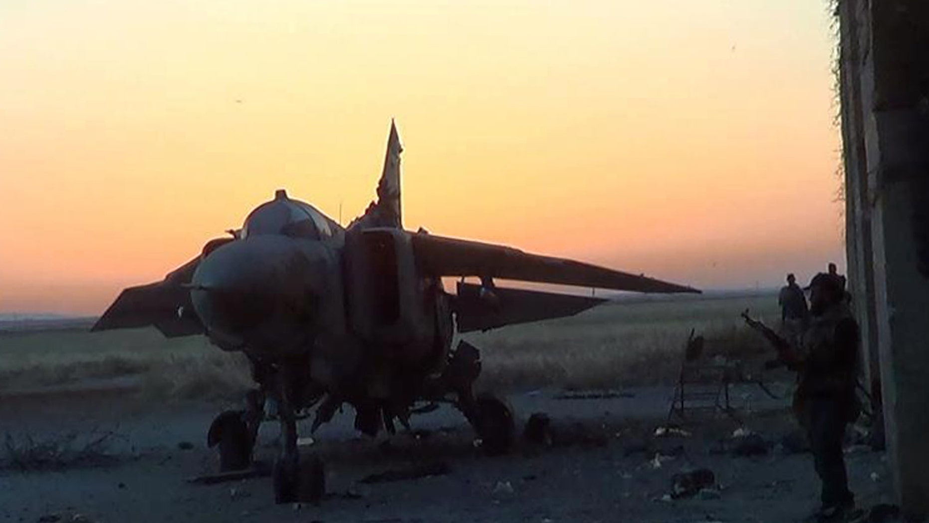 This citizen journalism image provided by The Syrian Revolution Against Bashar Assad which has been authenticated based on its contents and other AP reporting, shows Syrian rebels, right, standing near a damaged warplane, at Abu Dhour military airbase after it fell due to clashes with rebels, in the northern province of Idlib, Syria, Tuesday April 30, 2013.