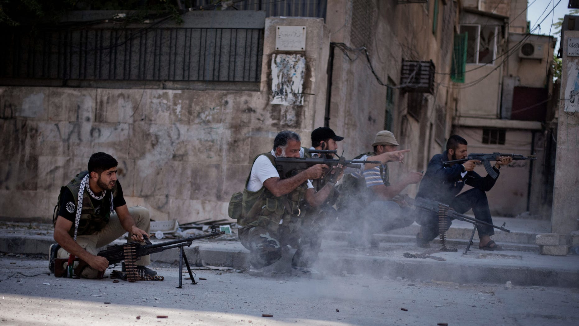 In this Saturday, Sept 8, 2012 photo, Free Syrian Army soldiers shoot their weapons towards Syrian Army positions in the Izaa district of Aleppo, Syria. Syrian activists say President Bashar Assad's regime pounded Aleppo with warplanes and artillery shelling Saturday as ground forces seeking to regain momentum in the country's largest city advanced on three neighborhoods. (AP Photo/Manu Brabo)