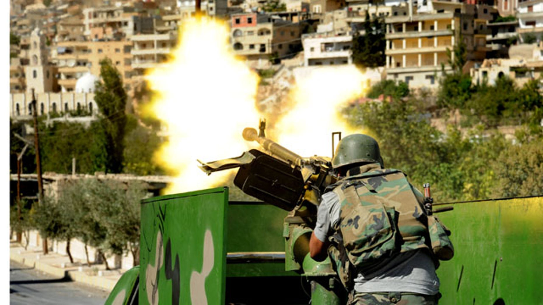 FILE -- In this Saturday, Sept. 7, 2013 file photo released by the Syrian official news agency SANA, a Syrian military solider fires a heavy machine gun during clashes with rebels in Maaloula village, northeast of the capital Damascus (AP Photo)