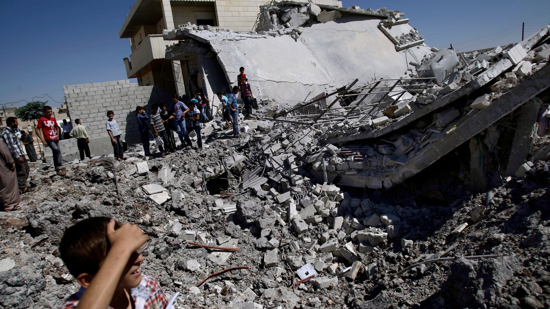 Sept. 3, 2012 - Syrians gather by the rubble of a house, destroyed from Syrian forces shelling in the Syrian town of Azaz, on the outskirts of Aleppo.