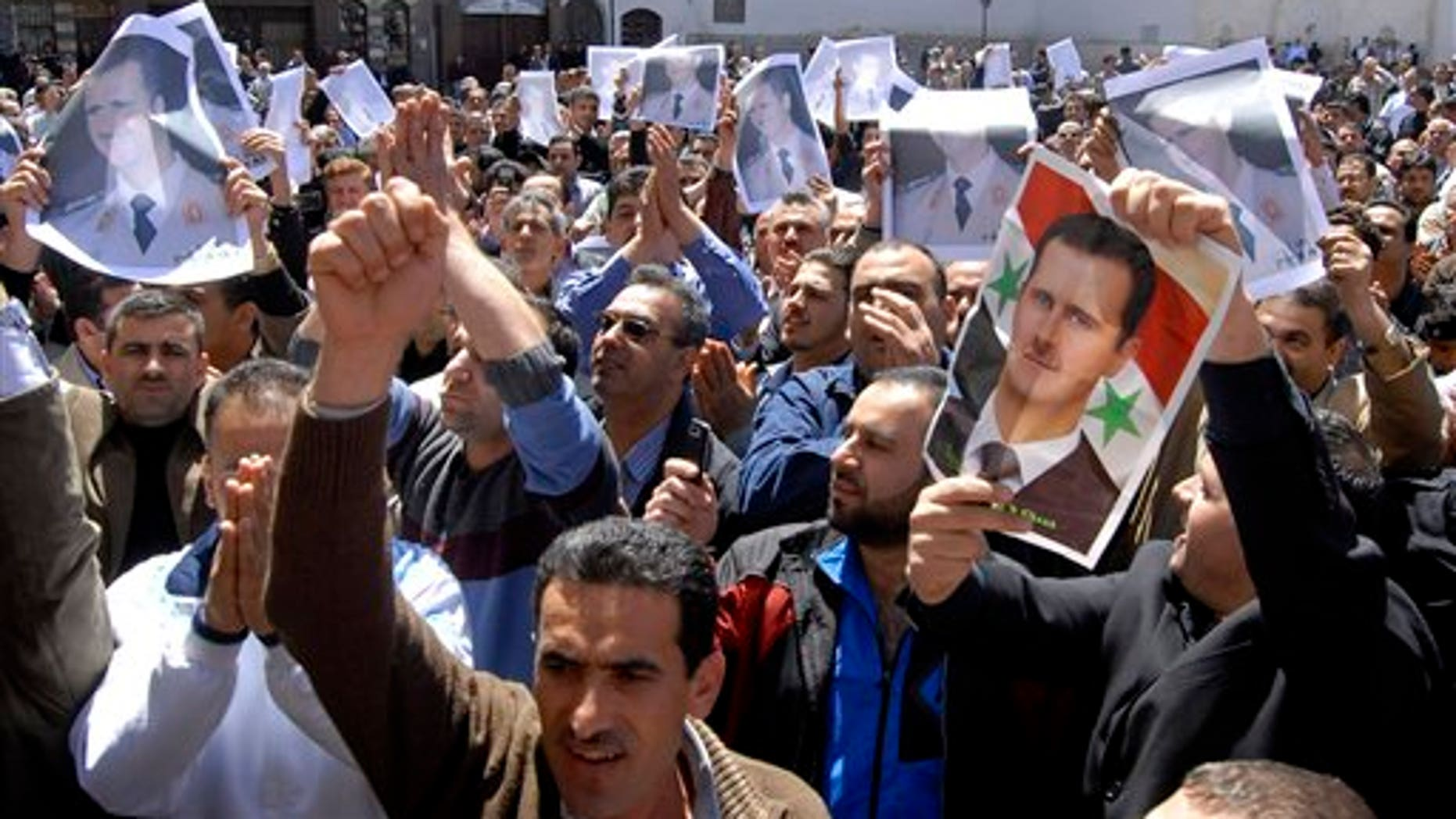April 15: Syrian pro-government protesters carry pictures of Syrian President Bashar Assad as they shout slogans after Friday prayers outside the Omayyad Mosque in Damascus, Syria. (AP)