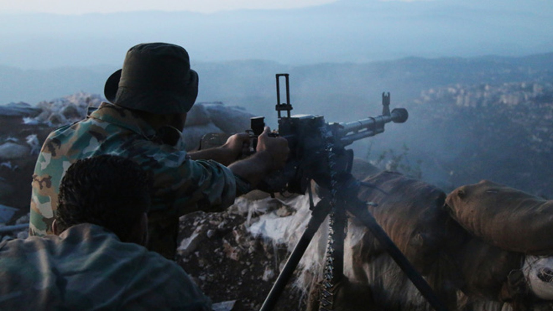 Oct. 10, 2015: Syrian army personnel fire a machine gun in Latakia province, about 12 miles from the border with Turkey, Syria.