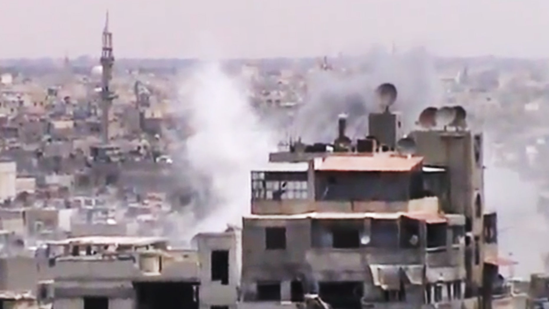 June 18, 2012: This image made from amateur video released by the Shaam News Network, purports to show smoke rising from buildings in Homs, Syria.
