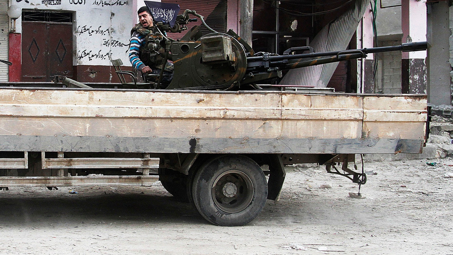 February 8, 2013-  Free Syrian Army fighter sits behind an anti-aircraft weapon in Aleppo, Syria.