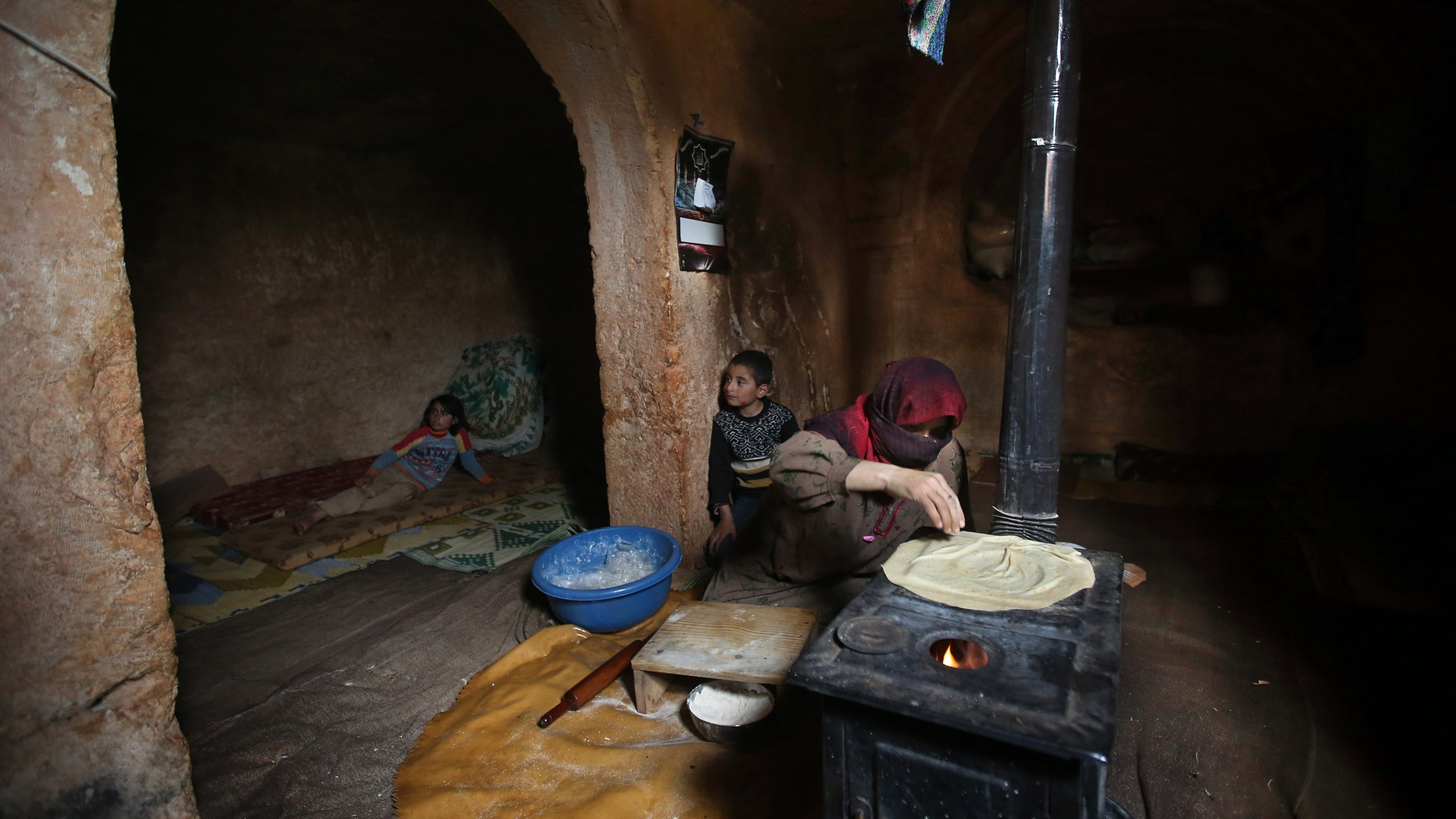 Feb. 28, 2013 - Nadia, 53, makes bread on a wooden stove, at an underground Roman tomb which she uses as a shelter with her family from Syrian government forces shelling and airstrikes.