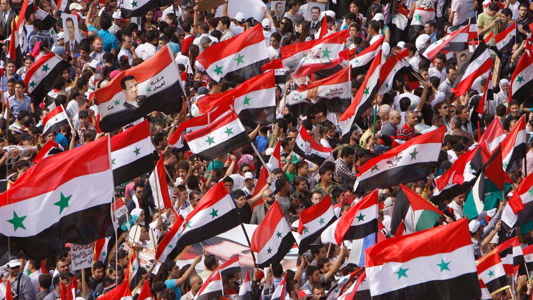 Syrian regime supporters wave their national flags during a demonstration to show their support for President Bashar Assad and to thanks Russia and China for blocking a U.N. Security Council resolution condemning Syria for its brutal crackdown, in Damascus, Syria, on Wednesday Oct. 12, 2011.