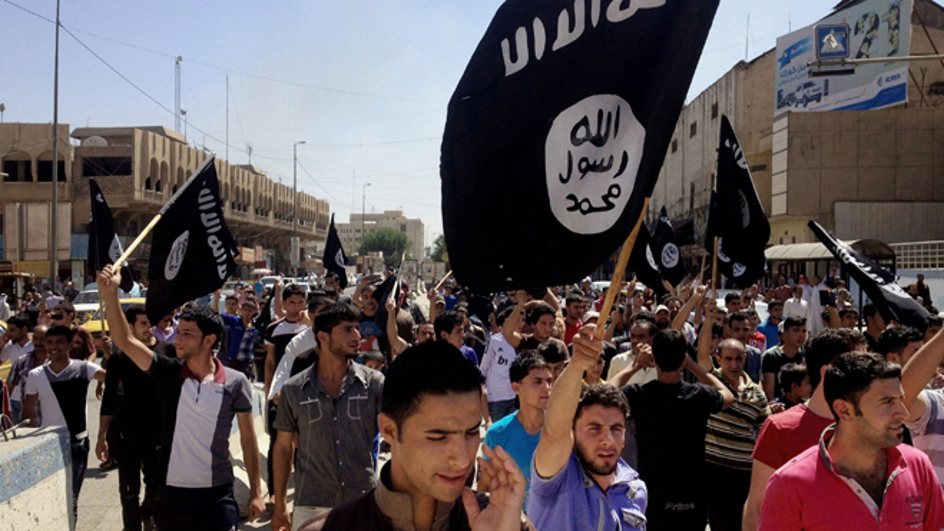 In this June 16, 2014 file photo, demonstrators chant pro-Islamic State group slogans as they carry the group's flags in front of the provincial government headquarters in Mosul, Baghdad.