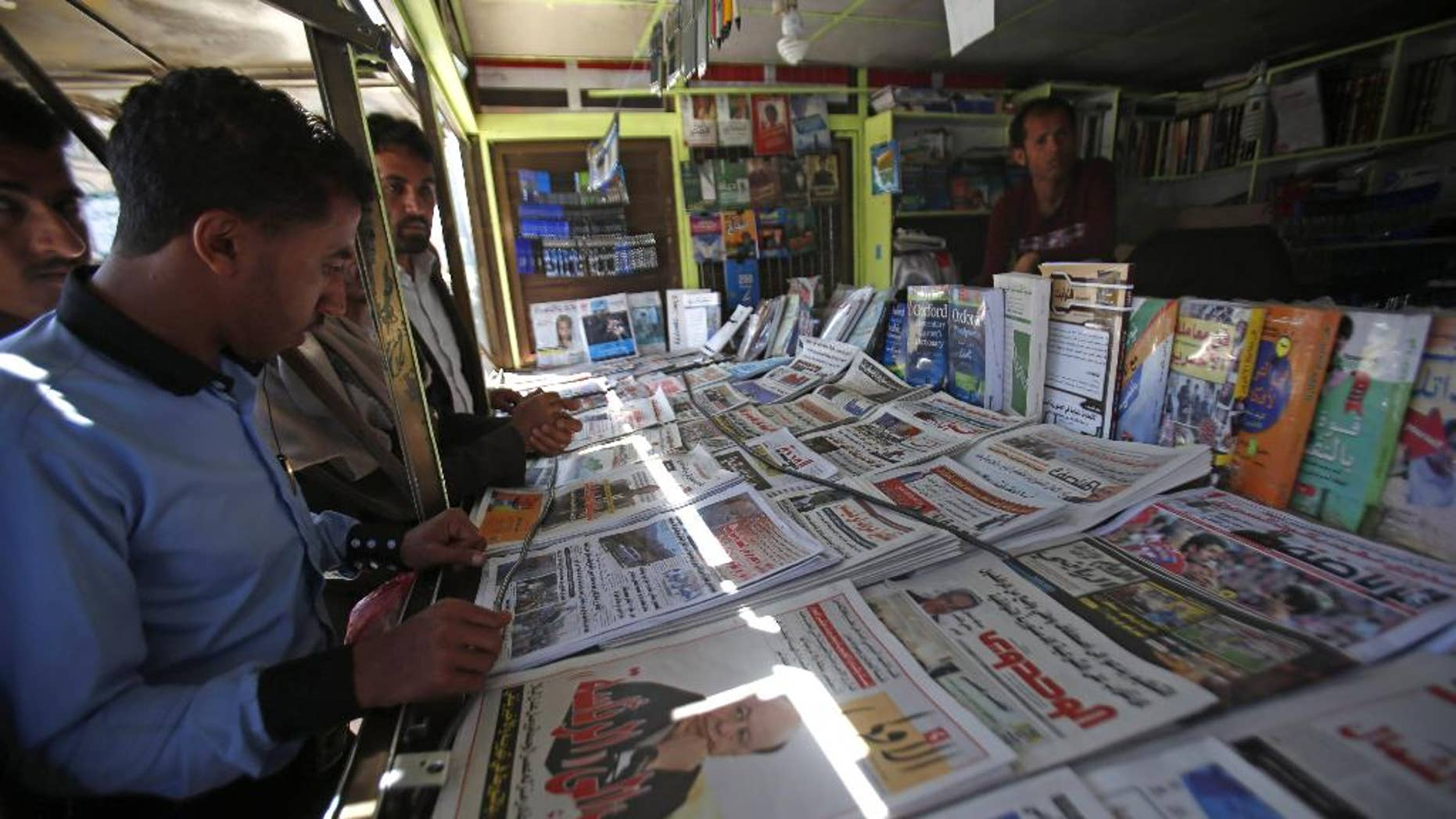 """A Yemeni man reads a newspaper featuring the front page with a photograph of former President Abed Rabbo Mansour Hadi, and a headline in Arabic that reads, """"he escaped to the presidency,"""" in Sanaa, Yemen, Sunday, Feb. 22, 2015. Virtually powerless for months, Yemen's overthrown President Hadi appeared ready to disappear from the country after fleeing Shiite rebels who held him captive in his own home. But the soft-spoken technocrat who long has avoided the limelight stepped back into it Saturday by renouncing his own resignation and challenging the Shiite Houthi rebels who hold control the capital and large parts of the country. (AP Photo/Hani Mohammed)"""