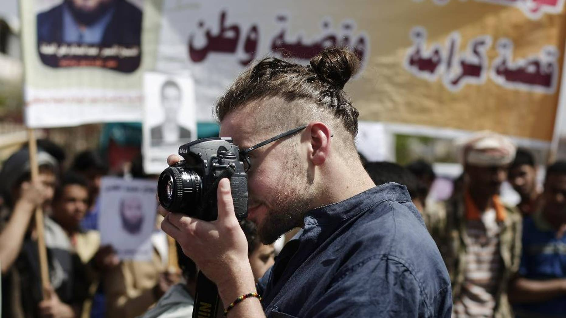 """In this Tuesday, April 16, 2013 photo, Luke Somers, 33, an American photojournalist who was kidnapped over a year ago by al-Qaida, uses a camera during a demonstration demanding the release of Yemeni detainees in Guantanamo Bay prison in front of the U.S. embassy in Sanaa, Yemen. Somers and a South African teacher held by al-Qaida militants in Yemen were killed Saturday, Dec. 6, 2014 during a U.S.-led rescue attempt, a raid President Barack Obama said he ordered over an """"imminent danger"""" to the reporter. (AP Photo/Hani Mohammed)"""
