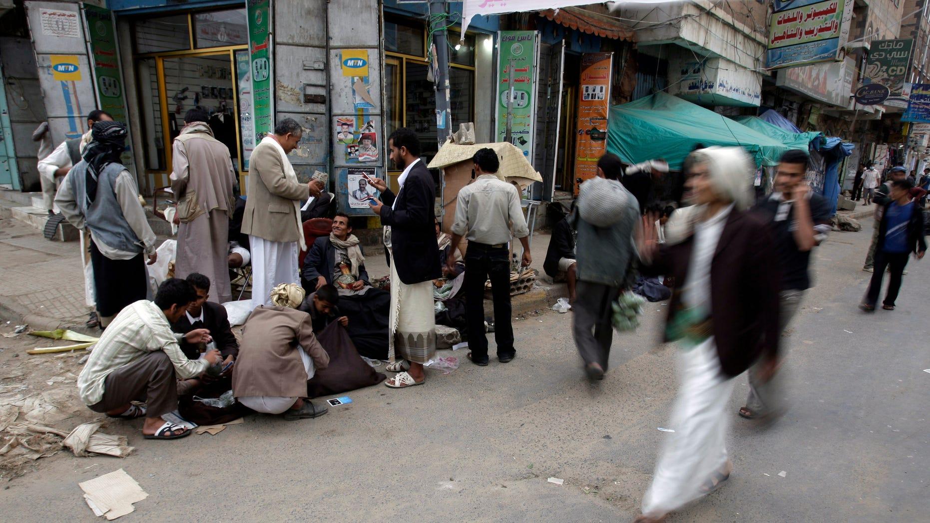 August 29: Yemenis walk past vendors selling Qat next to the site of anti-government protestors demanding the resignation of Yemen's President Ali Abdullah Saleh, in Sanaa, Yemen.