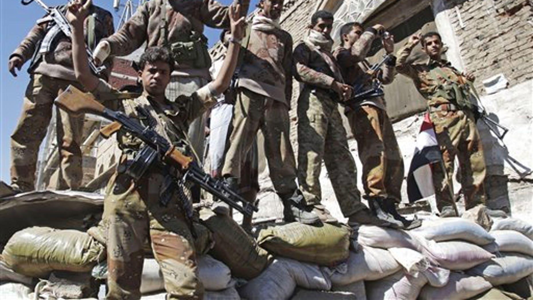 Dec. 25: Yemeni defected army soldiers gesture at protesters marching to demand the prosecution of Yemen's President Ali Abdullah Saleh in Sanaa, Yemen.