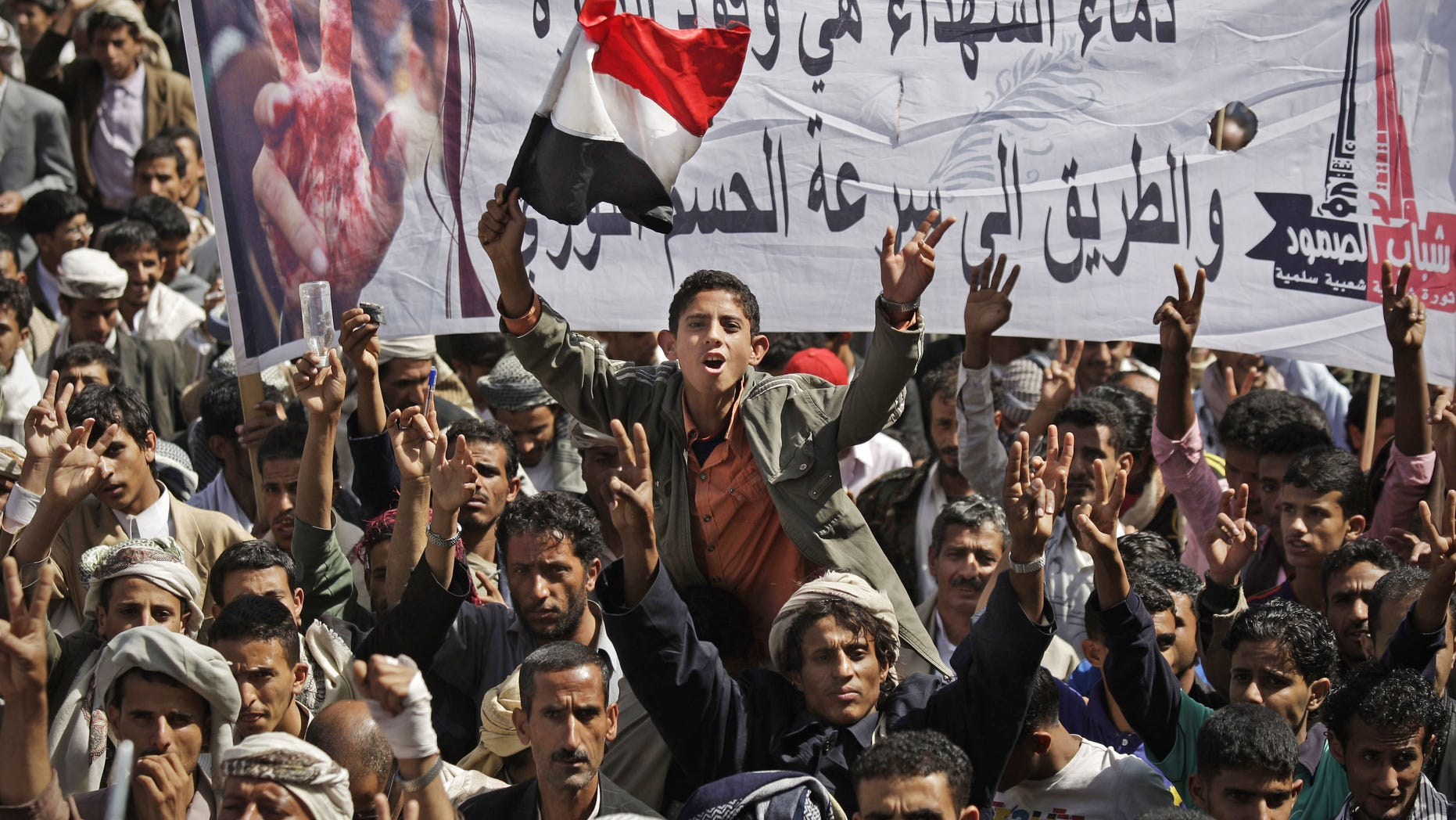 "November 10: Yemeni protestors chant slogans while holding up a banner that reads in Arabic, ""blood of the martyrs is the fuel of revolution, it's the way to get victory quickly,"" during a demonstration demanding the resignation of Yemeni President Ali Abdullah Saleh in Sanaa, Yemen."