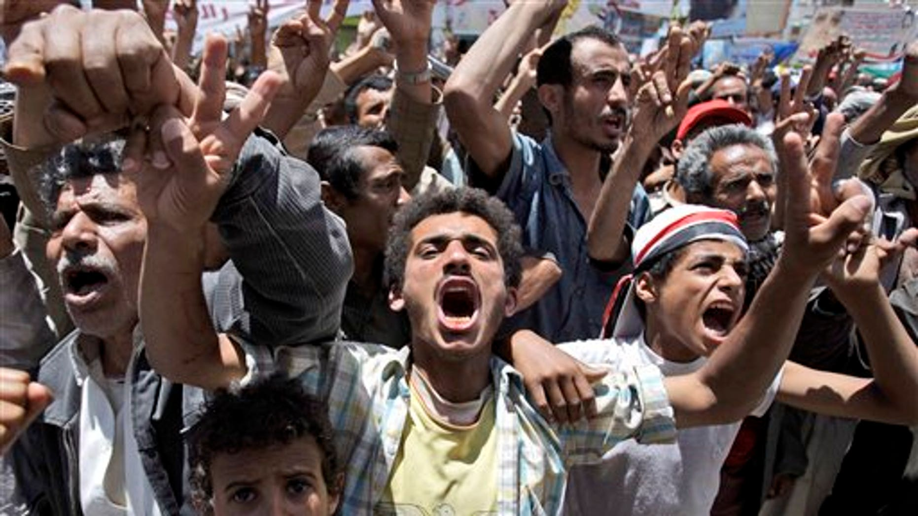 May 24: Anti-government protestors react during a demonstration demanding the resignation of Yemeni President Ali Abdullah Saleh, in Sanaa, Yemen. Fighters for Yemen's largest tribe sealed off key government buildings and barricaded streets in the heart of the capital Tuesday as the revolt against President Ali Abdullah Saleh sharply escalated after militiamen turned their guns against government forces. (AP)