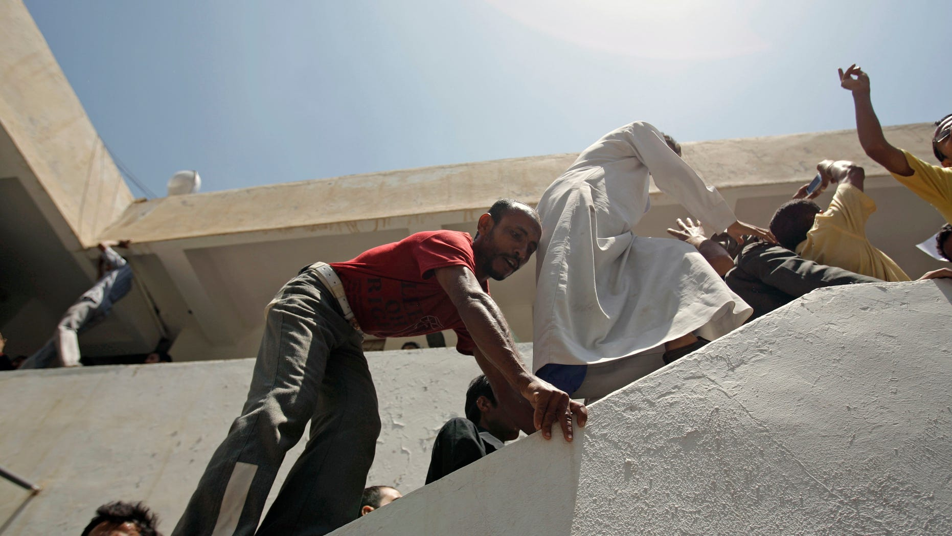 Students climb as they protest at the Sanaa University campus to show their support for a boycott of university studies as part of protests demanding the resignation of Yemeni President Ali Abdullah Saleh, in Sanaa,Yemen, Saturday, Sept. 17, 2011.