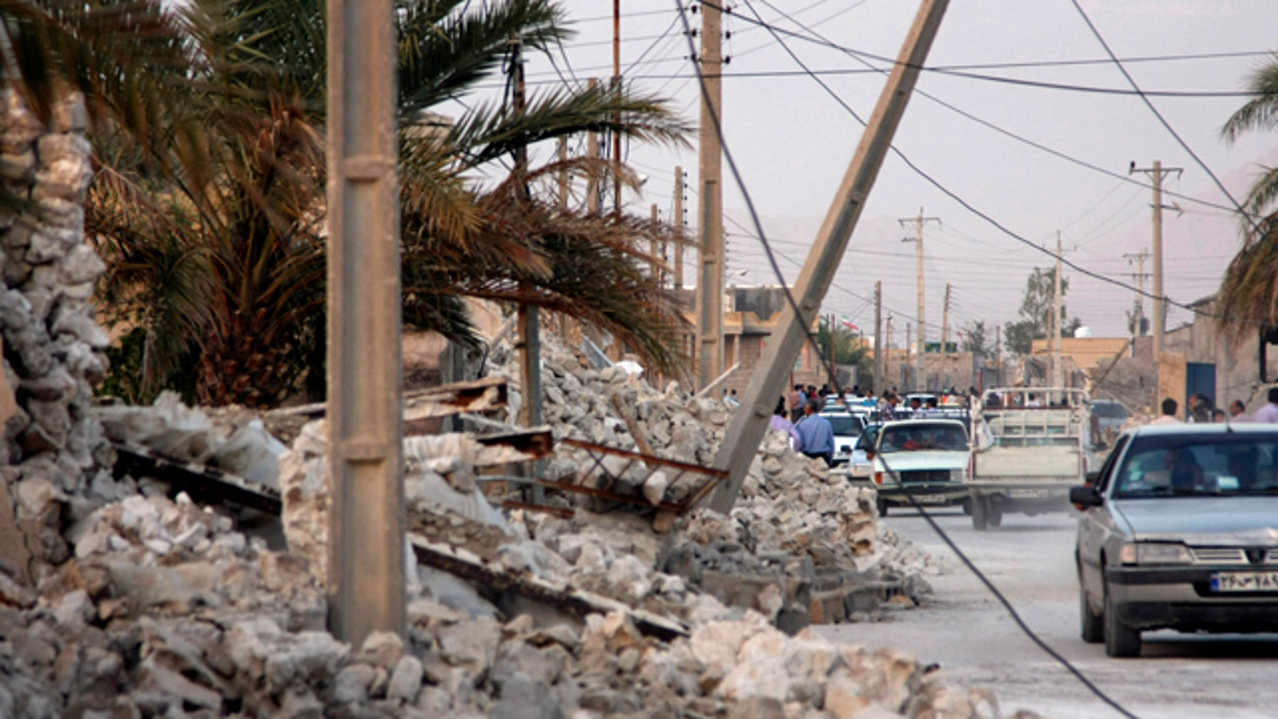 April 9, 2013: Vehicles make their way along structures destroyed by an earthquake which struck southern Iran in the city of Shonbeh, Iran.