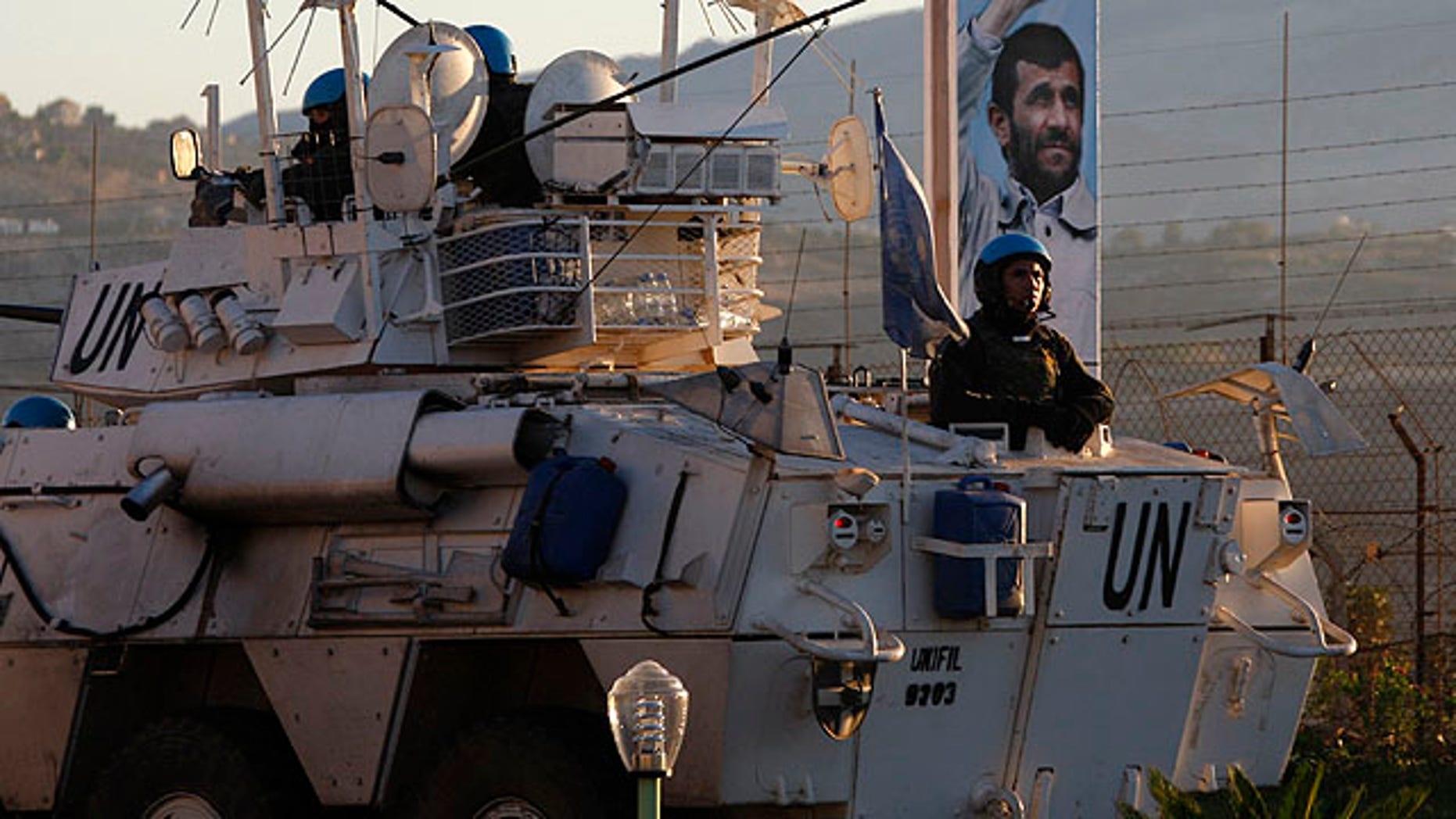 Oct. 12, 2010: U.N. peacekeepers patrol the border in front of an attached picture of Iranian President Mahmoud Ahmadinejad, a day ahead of his visit, in the southern border village of Kfar Kila, Lebanon.