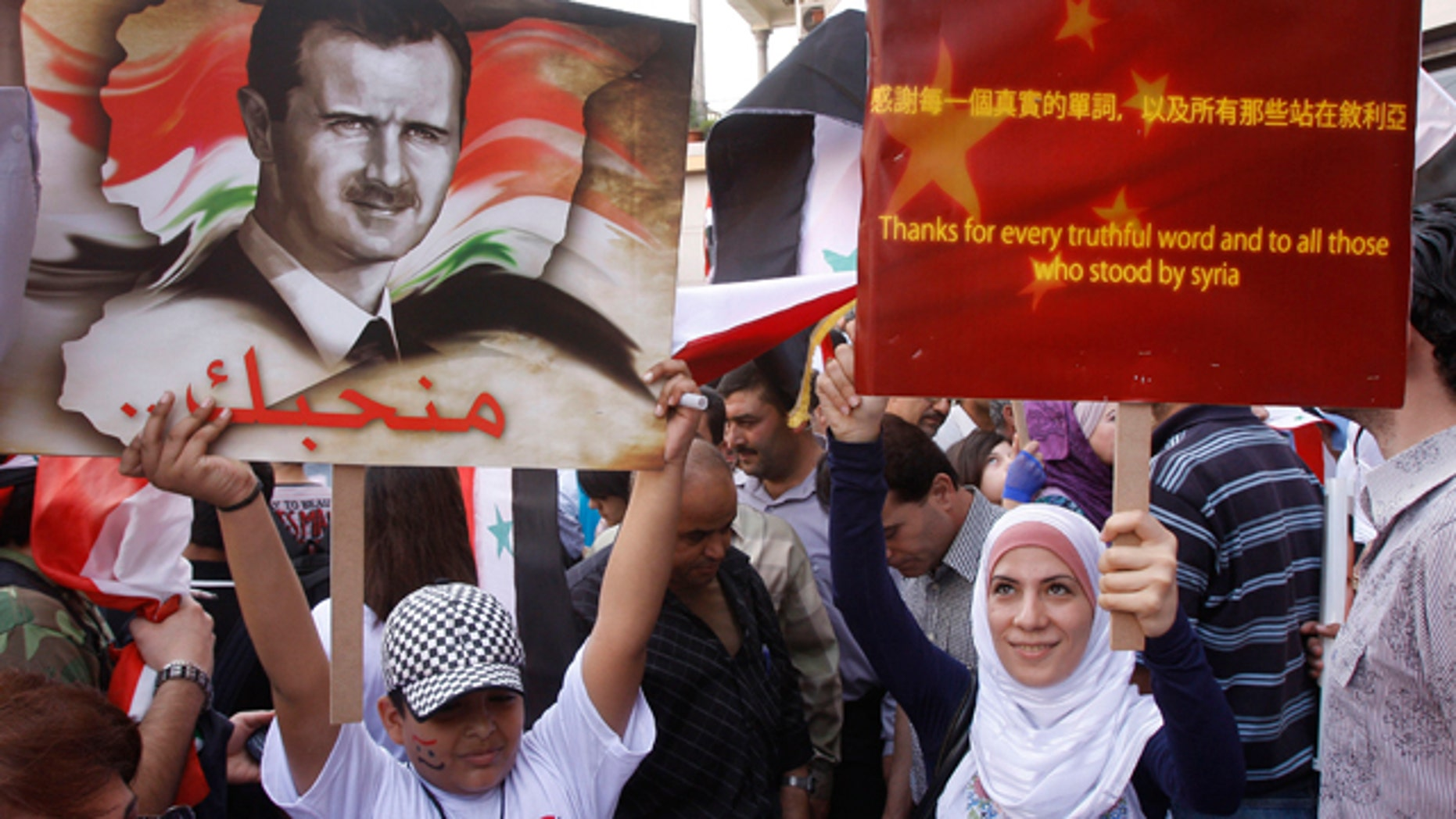 Syrian regime supporters holds up pro-China placard during a demonstration to show their support for President Bashar Assad and to thank Russia and China for blocking a U.N. Security Council resolution condemning Syria for its brutal crackdown, in Damascus, Syria.