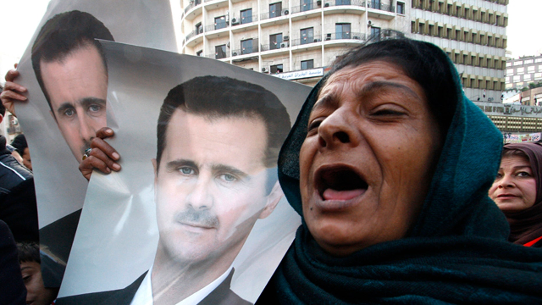 Wed. Jan 25, 2012: Pro-Syrian regime protesters, shout slogans and holds portrait of Syrian President Bashar Assad during a demonstration to show their solidarity for their president, in Damascus, Syria. Government forces clashed with army defectors and stormed rebellious districts in central Syria on Wednesday, firing mortars and deploying snipers in violence that killed at least seven people, including a mother and her 5-year-old child, activists said. (AP Photo)