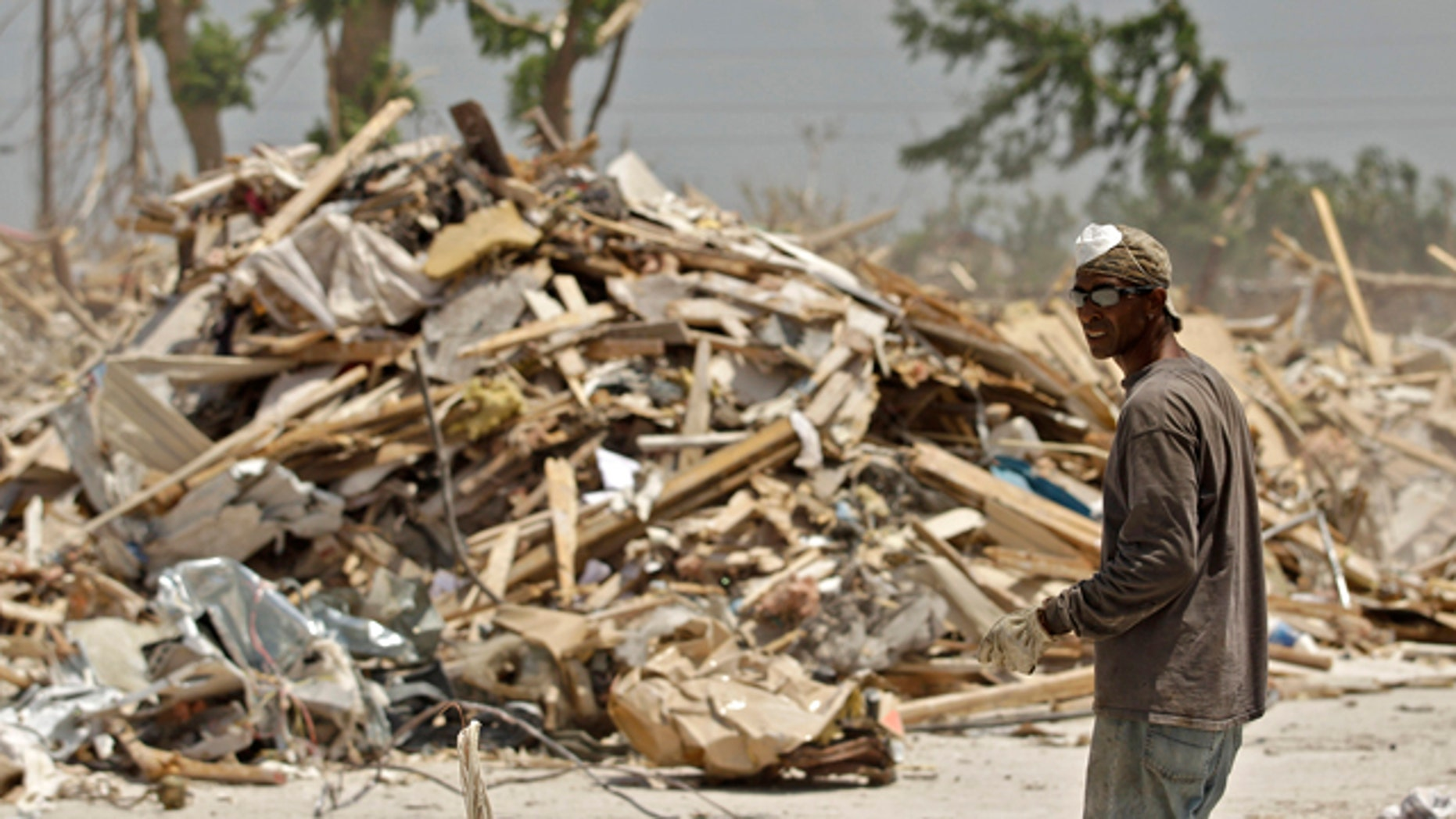 July 20: A worker salvages metal from debris at an apartment complex destroyed by Joplin's tornado.