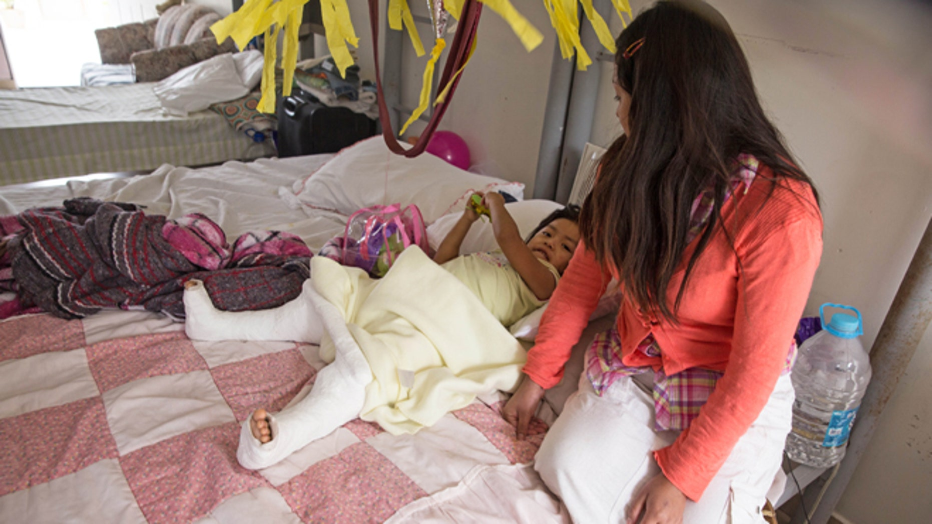 """In this Dec. 15, 2015, photo, Marleny Gonzalez, right, looks at her 4-year-old daughter, Jenifer, at a shelter in Reynosa, Mexico, where they are living after trying to cross in to the United States. Gonzalez said her daughter suffered two broken legs when a truck they were traveling in overturned on the journey from Guatemala. âAlmost all my family is in the United States,â Gonzalez said, including her daughterâs father. âI felt alone,"""" she said. Given her daughterâs precarious state, she wasnât sure whether she would make the rest of the trip. (AP Photo/Seth Robbins)"""