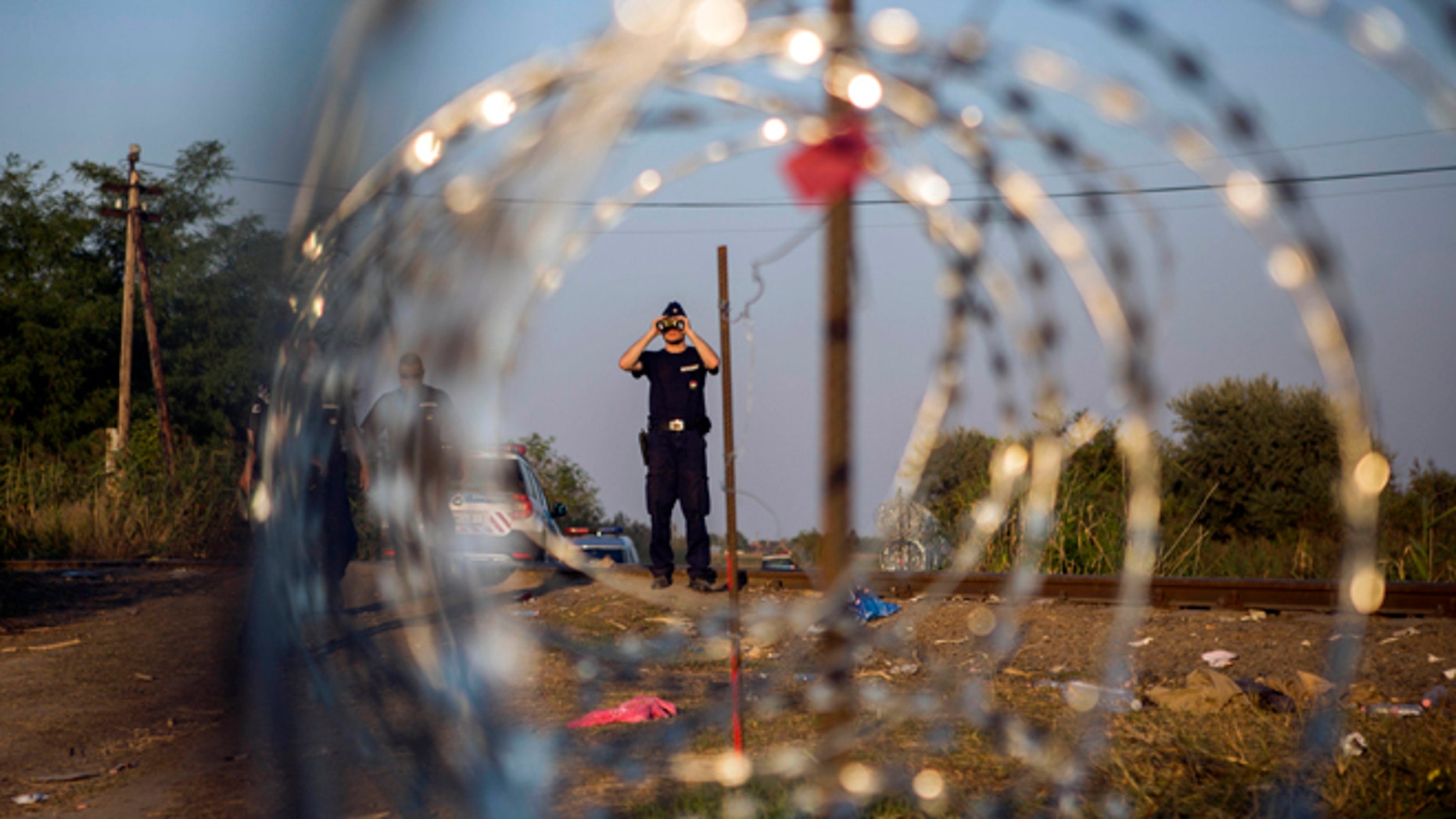 FILE - In this Tuesday, Sept. 1, 2015 file photo, a Hungarian police officer looks through binoculars as he checks the border for refugees entering the country illegally next to the town of Roszke, Hungary. In the 28-nation EU, some countries have sought to block the unprecedented flow of migrants fleeing war or poverty in the Middle East and Africa. (AP Photo/Santi Palacios, File)