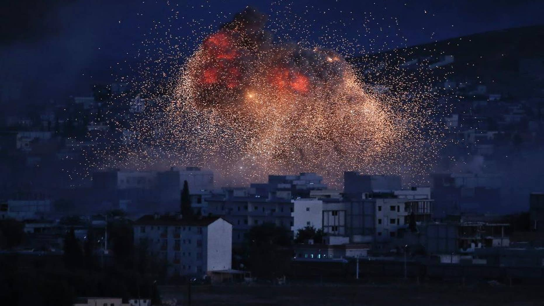 FILE - In this Monday, Oct. 20, 2014 file photo, thick smoke and flames from an airstrike by the U.S.-led coalition rise in Kobani, Syria, as seen from a hilltop on the outskirts of Suruc, at the Turkey-Syria border. Al-Qaida is using U.S. airstrikes in Syria as a reason to extend olive branches to the renegade Islamic State group, saying the two should stop feuding and join forces to attack Western targets,  a reunification that intelligence analysts say would allow al-Qaida to capitalize on the younger group's ruthless advance across the region. (AP Photo, Lefteris Pitarakis, File)