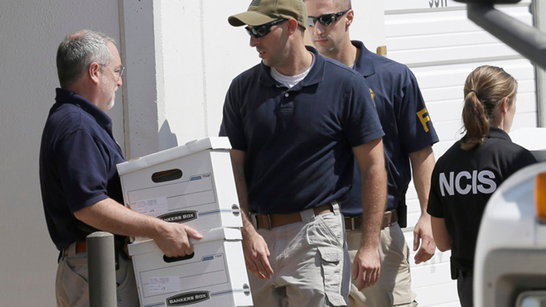 Oct. 3, 2012: Federal agents carry boxes out of Arc Electronics Inc. , in Houston.