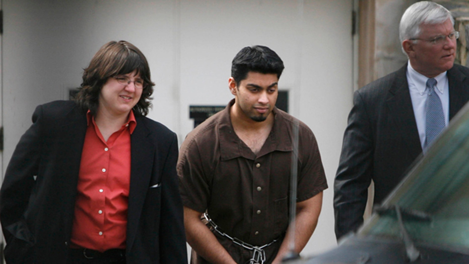 In this March 21, 2007 photo, taken through a fence, Khaleel Ahmed, 26, of Chicago, is led out of the Federal Courthouse in Toledo, Ohio, by a federal agent and accompanied by an attorney.  (AP)