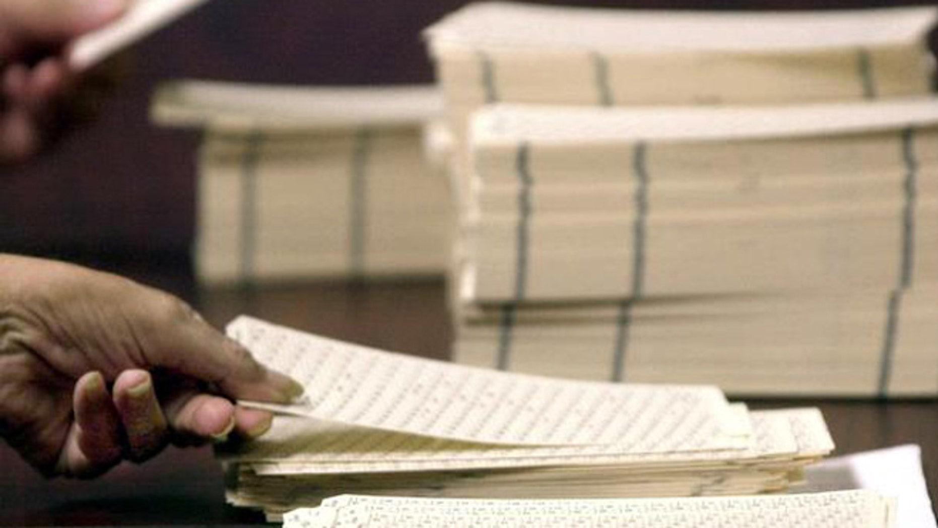 FILE: January 2000: Worker handles Broward County overseas absentee ballots during manual recount, Florida.
