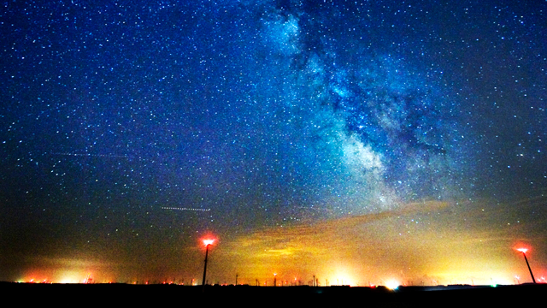 The Milky Way spins in the sky above wind turbines near Lake Benton and Hendricks, Minn. Scientists have estimated the first cosmic census of planets in our galaxy and the numbers are astronomical: at least 50 billion planets in the Milky Way. At least 500 million of those planets are in the not-too-hot, not-too-cold zone where life could exist, scientists announced Saturday, Feb. 19, 2011.