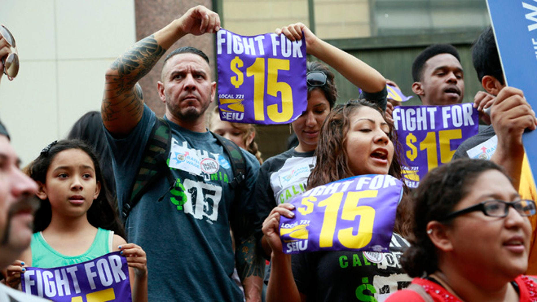 FILE - In this Tuesday, July 21, 2015 file photo, workers hold a rally in Los Angeles in support of the Los Angeles County Board of Supervisors' proposed minimum wage ordinance. On Saturday, March 26, California legislators and labor unions reached an agreement that will take the state's minimum wage from $10 to $15 an hour. (AP Photo/Nick Ut)