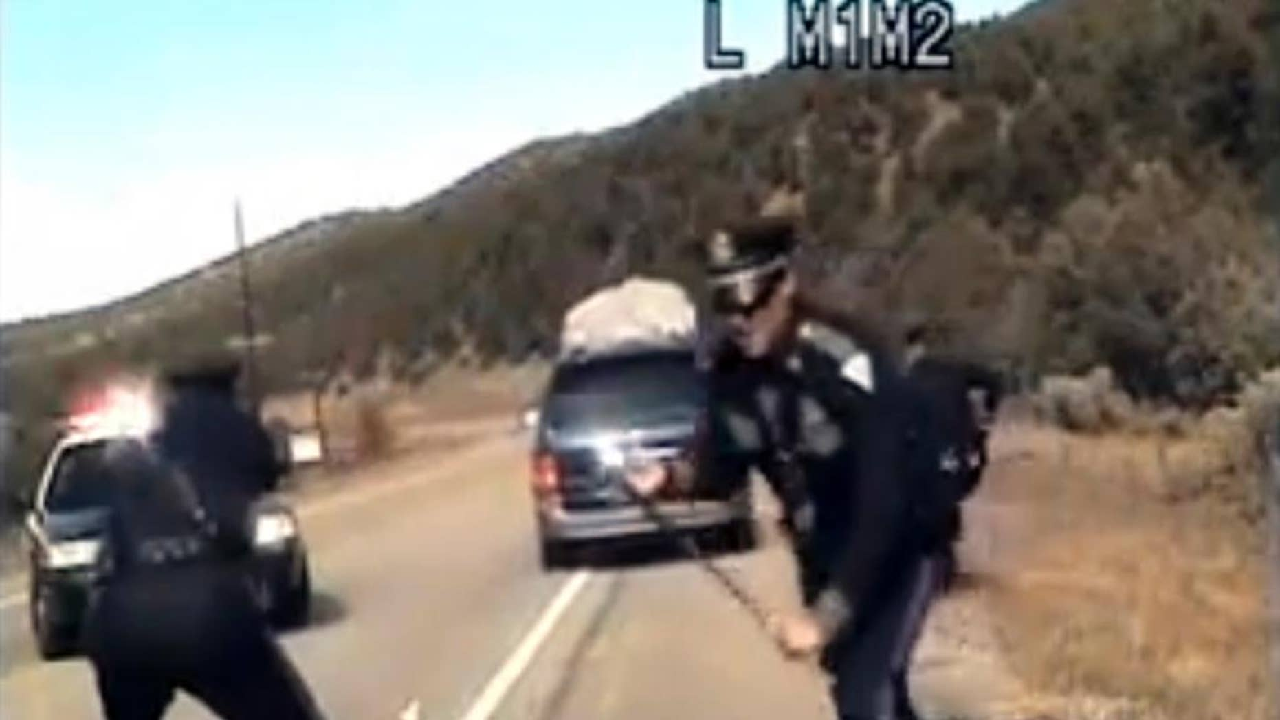 FILE - This file image from video provided by the New Mexico State Police shows three New Mexico State Police officers reacting as a minivan driven by motorist Oriana Farrell pulls away from a traffic stop on Oct. 28, 2013. New Mexico prosecutors aim to file new charges against Farrell in the chaotic traffic stop and chase last year during which a New Mexico State Police officer fired shots at her minivan full of children. The New Mexico Court of Appeals recently tossed Farrell's charges, including fleeing an officer and child abuse. (AP Photo/New Mexico State Police, File)