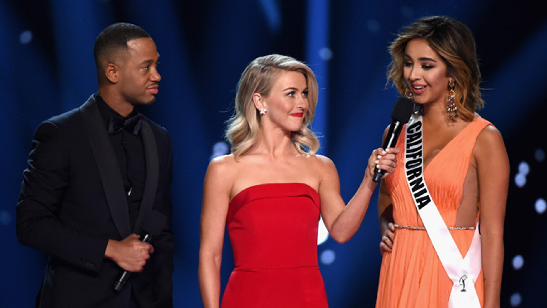 LAS VEGAS, NV - JUNE 05:  Miss California USA 2016 Nadia Mejia (R) competes in the interview portion as hosts Terrence J (L) and Julianne Hough (C) speak onstage during the 2016 Miss USA pageant at T-Mobile Arena on June 5, 2016 in Las Vegas, Nevada.  (Photo by Ethan Miller/Getty Images)