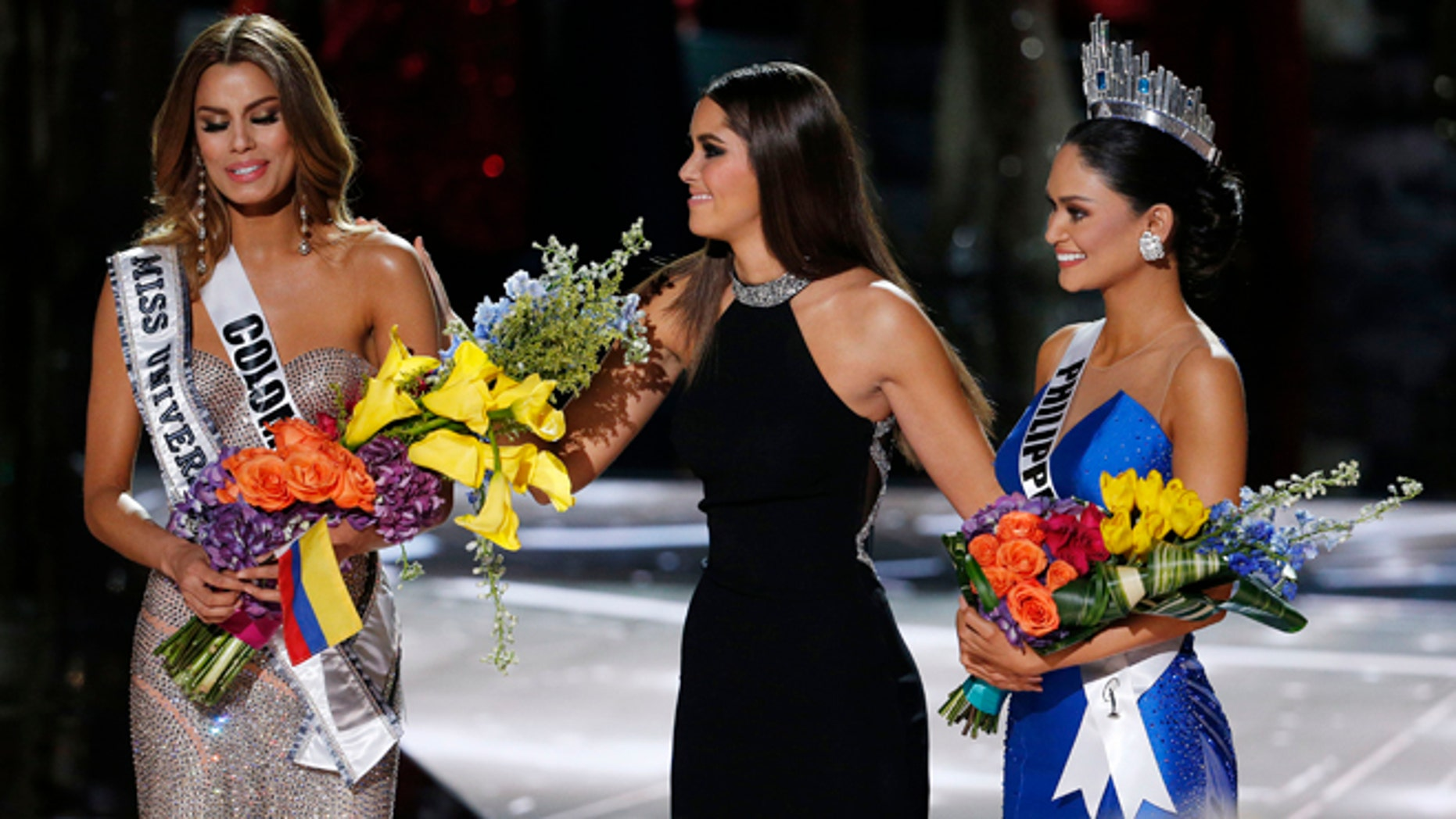 Former Miss Universe Paulina Vega takes away the flowers and sash from Miss Colombia Ariadna Gutierrez before giving them to Miss Philippines Pia Alonzo Wurtzbach on Sunday, Dec. 20, 2015.