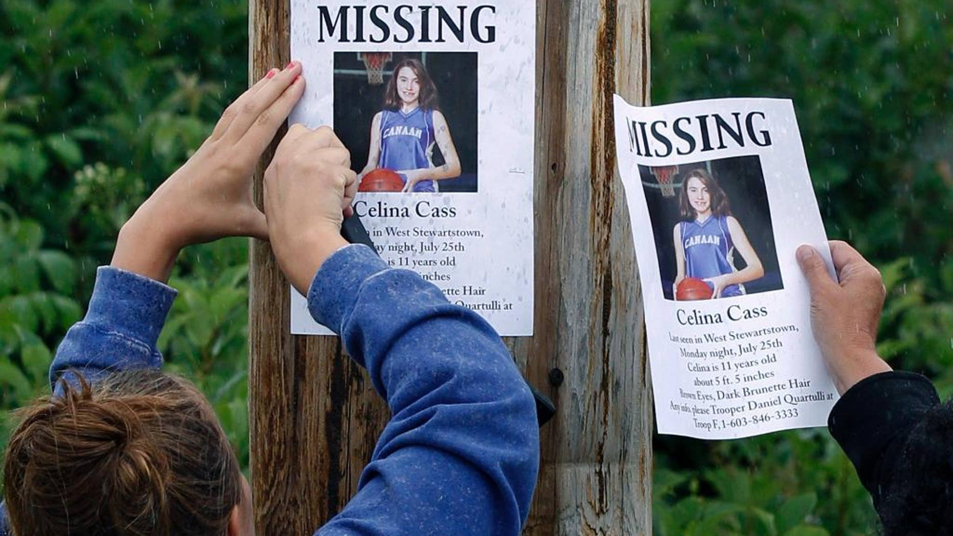 FILE - In this July 28, 2011 file photo, Kaylin Pettit, of Stewartstown, N.H., left, and Lori McKearney, of Lancaster, N.H. tack missing posters for Celina Cass to a utility pole in Colebrook, N.H.  A week after Cass went missing from her family's West Stewartstown apartment on July 25, 2011, her body was found near a dam in the Connecticut River. Four years later, no one has been charged with her death, which investigators have called a homicide. (AP Photo/Charles Krupa, File)