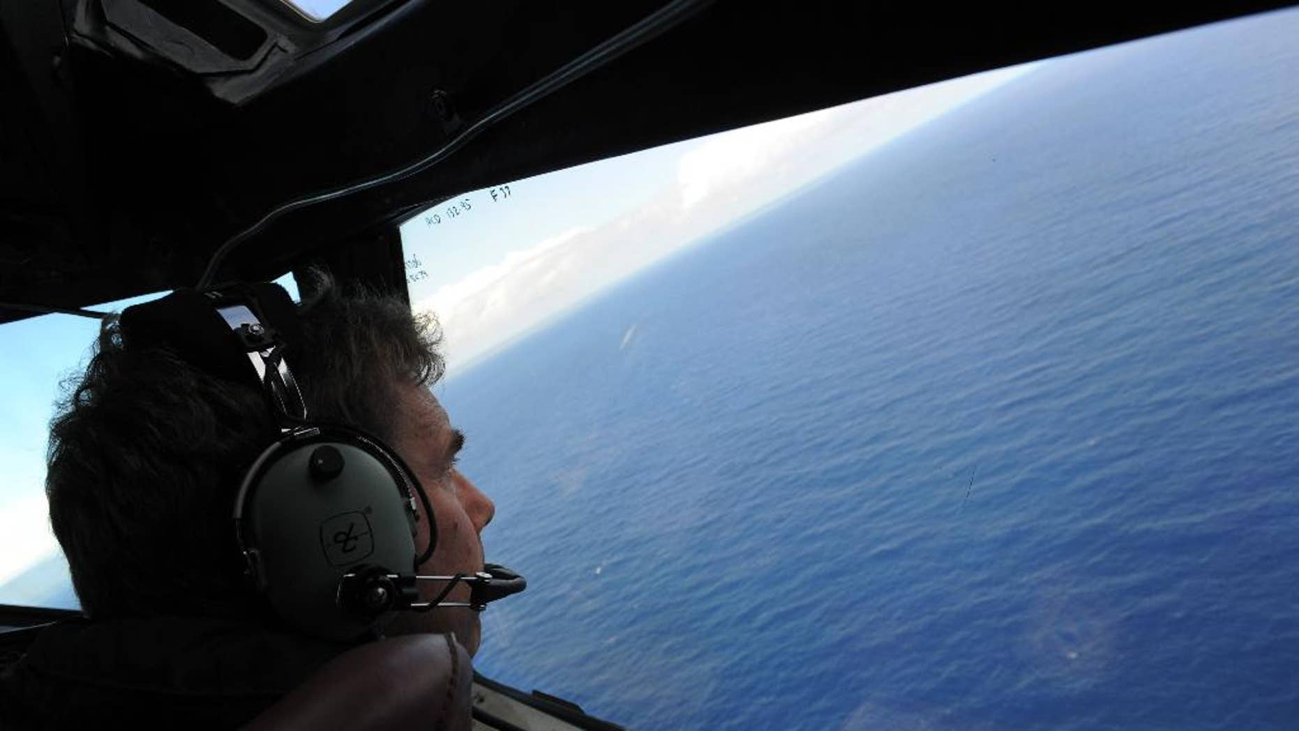 FILE - In this April 13, 2014, file photo taken from the Royal New Zealand air force (RNZAF) P-3K2-Orion aircraft, co-pilot Squadron Leader Brett McKenzie looks out of a window while searching for debris from missing Malaysia Airlines Flight 370, in the Indian Ocean off the coast of western Australia.  Even with the recent discovery of a possible wing fragment from the missing airplane on Wednesday, July 29, 2015,  on a remote island in the Indian Ocean, tracing the route of the debris back across Indian Ocean may prove impossible. (Greg Wood/Pool Photo via AP)