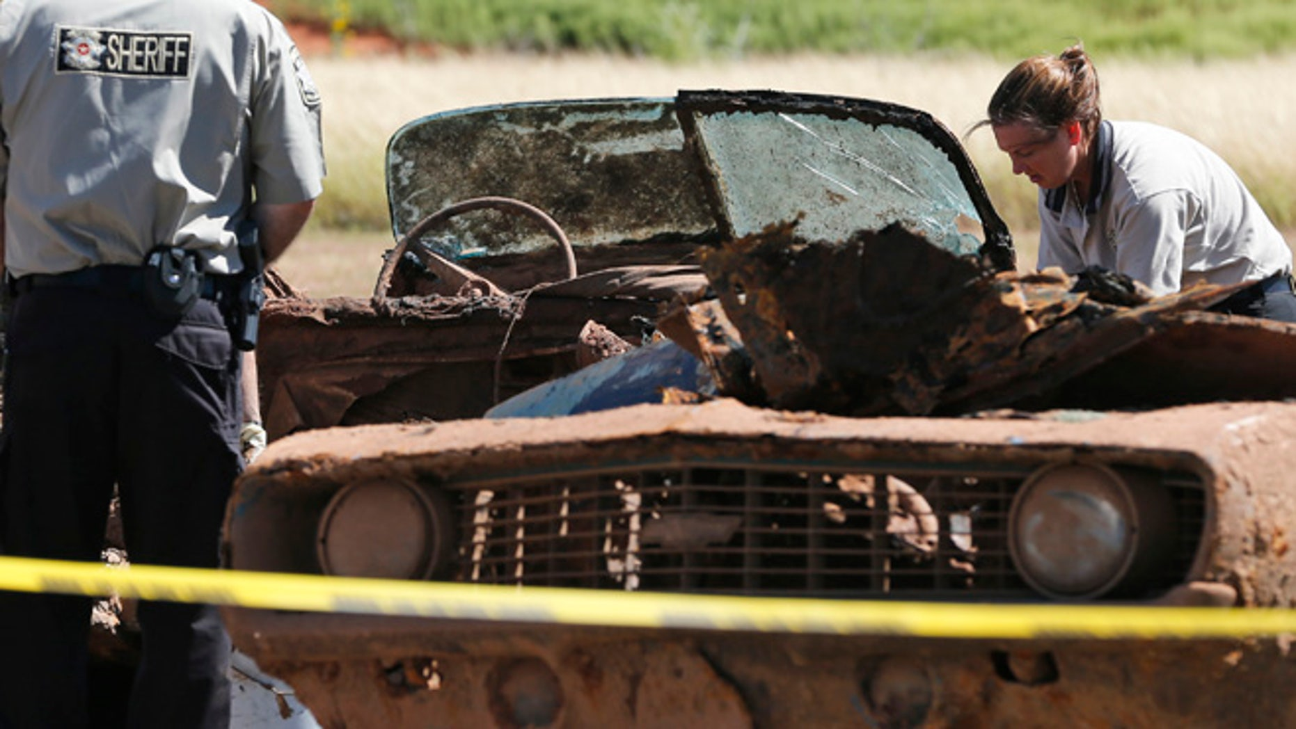 Officials work on the second of two cars found in Foss Lake in Foss, Okla., Wednesday, Sept. 18, 2013.