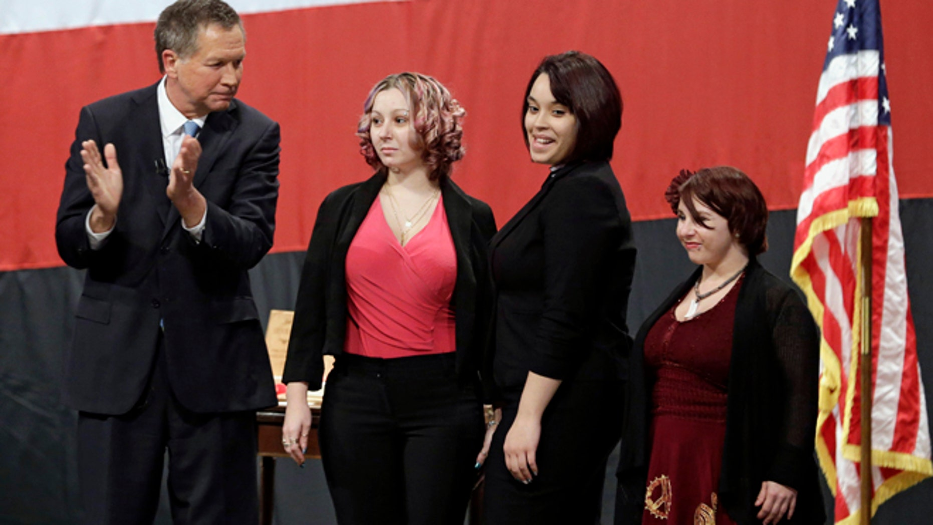 FILE- This Monday, Feb. 24, 2014 file photo shows Ohio Gov. John Kasich, from left, introducing Amanda Berry, Gina DeJesus and Michelle Knight during his State of the State address at the Performing Arts Center in Medina, Ohio. Berry broke through a screen door to freedom last May. Upstairs, officers found DeJesus and Knight. They had been snatched off the streets separately between 2002 and 2004 and locked inside Castroâs house where he chained and raped them, investigators later said. (AP Photo/Tony Dejak, File)