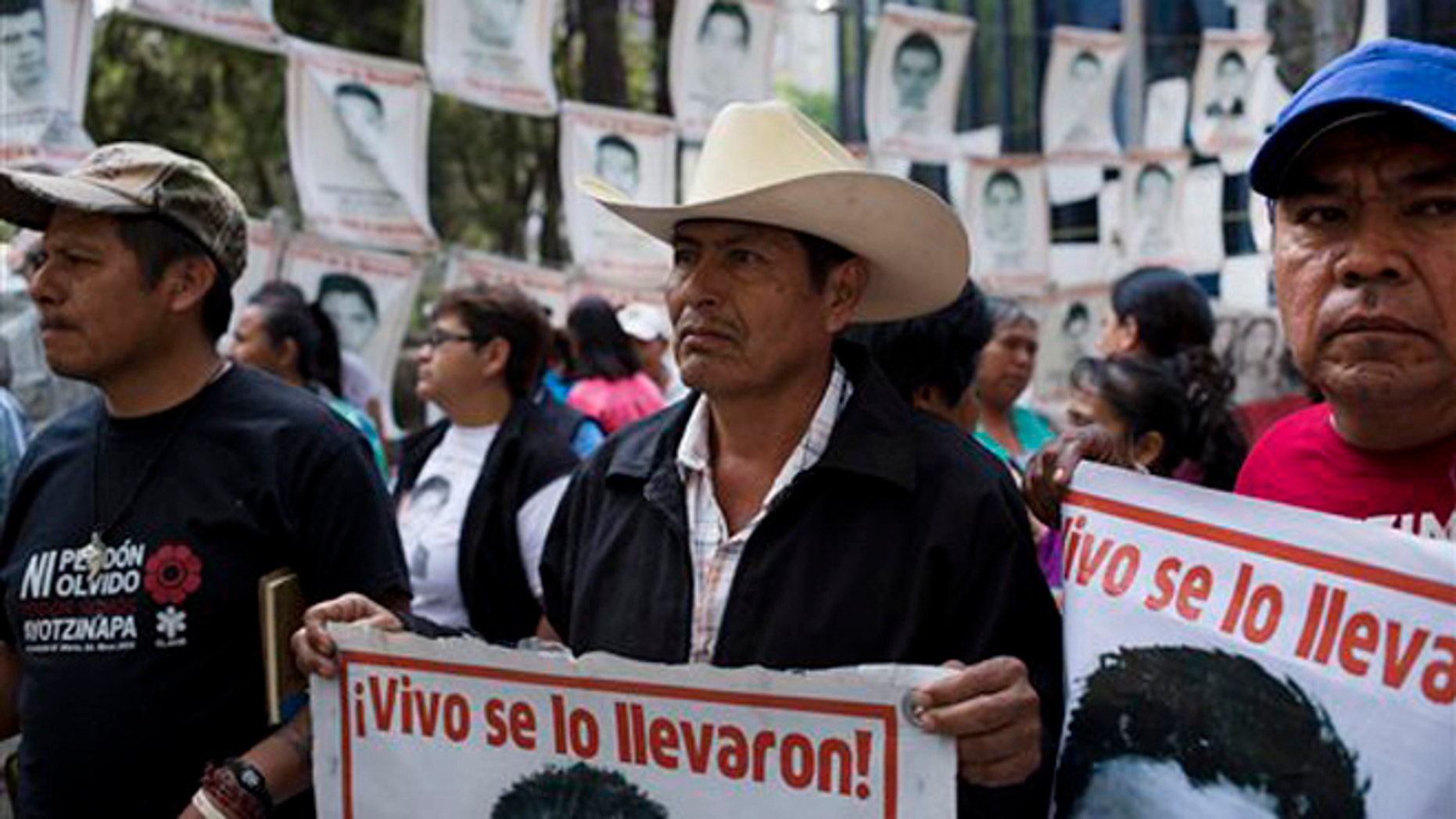 """Relatives of 43 missing students from the Isidro Burgos rural teachers' college hold pictures of their missing loved ones after meeting with  Attorney General Arely Gomez Gonzalez in Mexico City, Thursday, March 17, 2016. His sign reads in Spanish: """"They took them alive!."""" In September of 2014, several students and bystanders were killed and 43 students vanished in the city of Iguala, allegedly taken by police and then handed over to a criminal gang who burned their bodies in a garbage dump, according to a federal investigation. Families of the missing and independent investigators cast doubts on the official version. (AP Photo/Eduardo Verdugo)"""