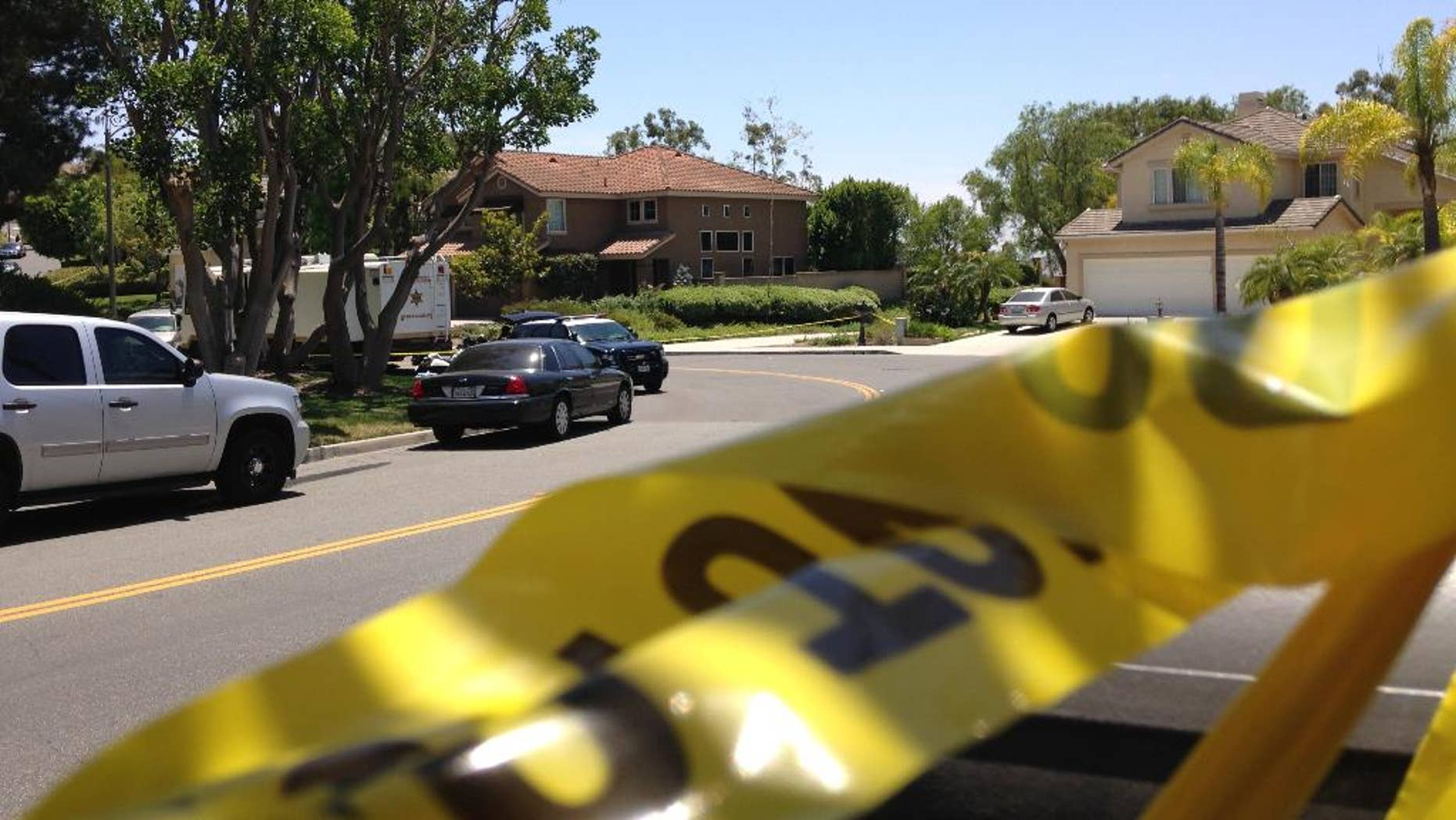 Police tape closes a street where four people were found dead in a home, center, on Tuesday, May 27, 2014 in suburban Mission Viejo, Calif. Authorities said the bodies were found by Orange County deputies making a welfare check after a relative's emergency call. The dead people were only described as two males and two females, and the Sheriff's Department was not releasing any information on how they may be related.(AP Photo/Gillian Flaccus)