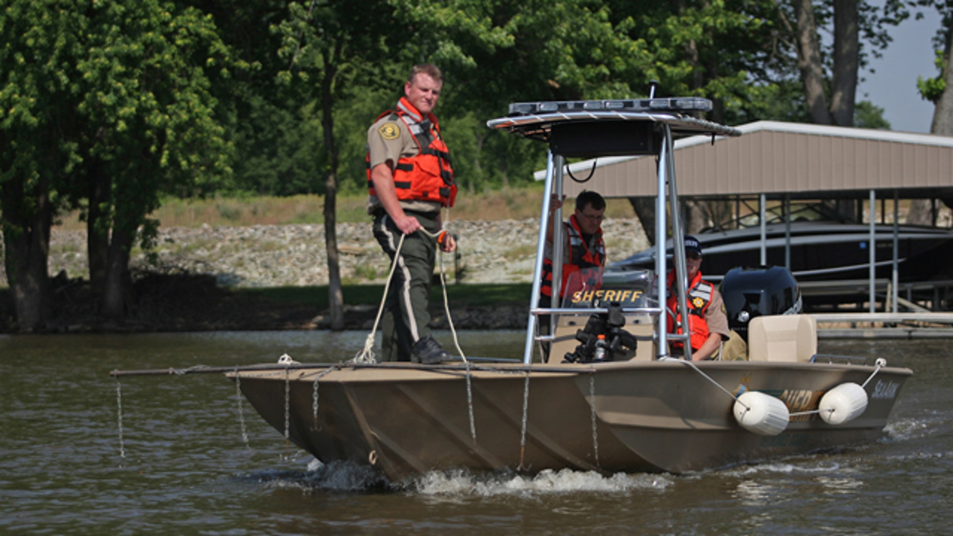 May 19, 2012: Des Moines County officer Kevin Glendening, foreground, drags the Mississippi River as officer Brad Siegfried, center, and Sheriff Mike Johnstone use sonar to locate four missing people near O'Connel Slough near Burlington, Iowa.