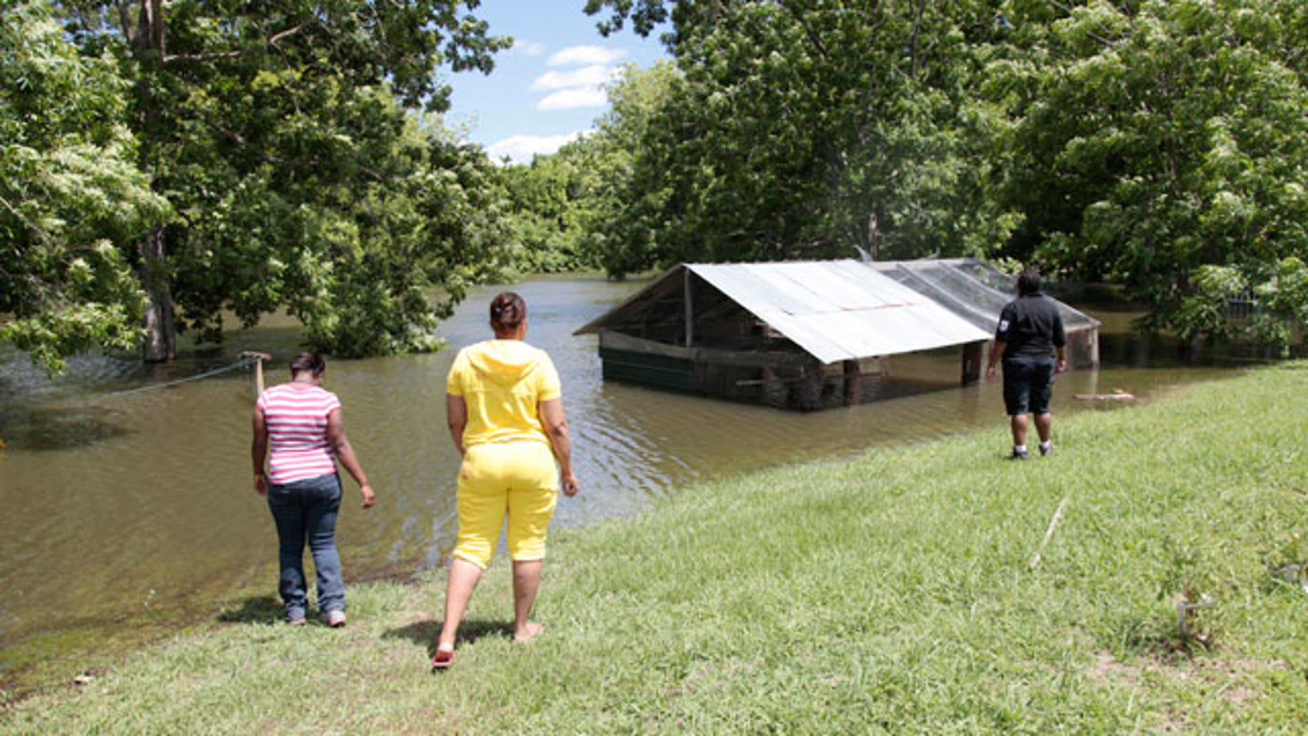 Sherrel Hall, right, and Debra Prater, left, look at rising floodwaters from the Atchafalaya River as it encroaches on a shed where camps and homes sit in Simmesport, La., Monday, May 16, 2011.