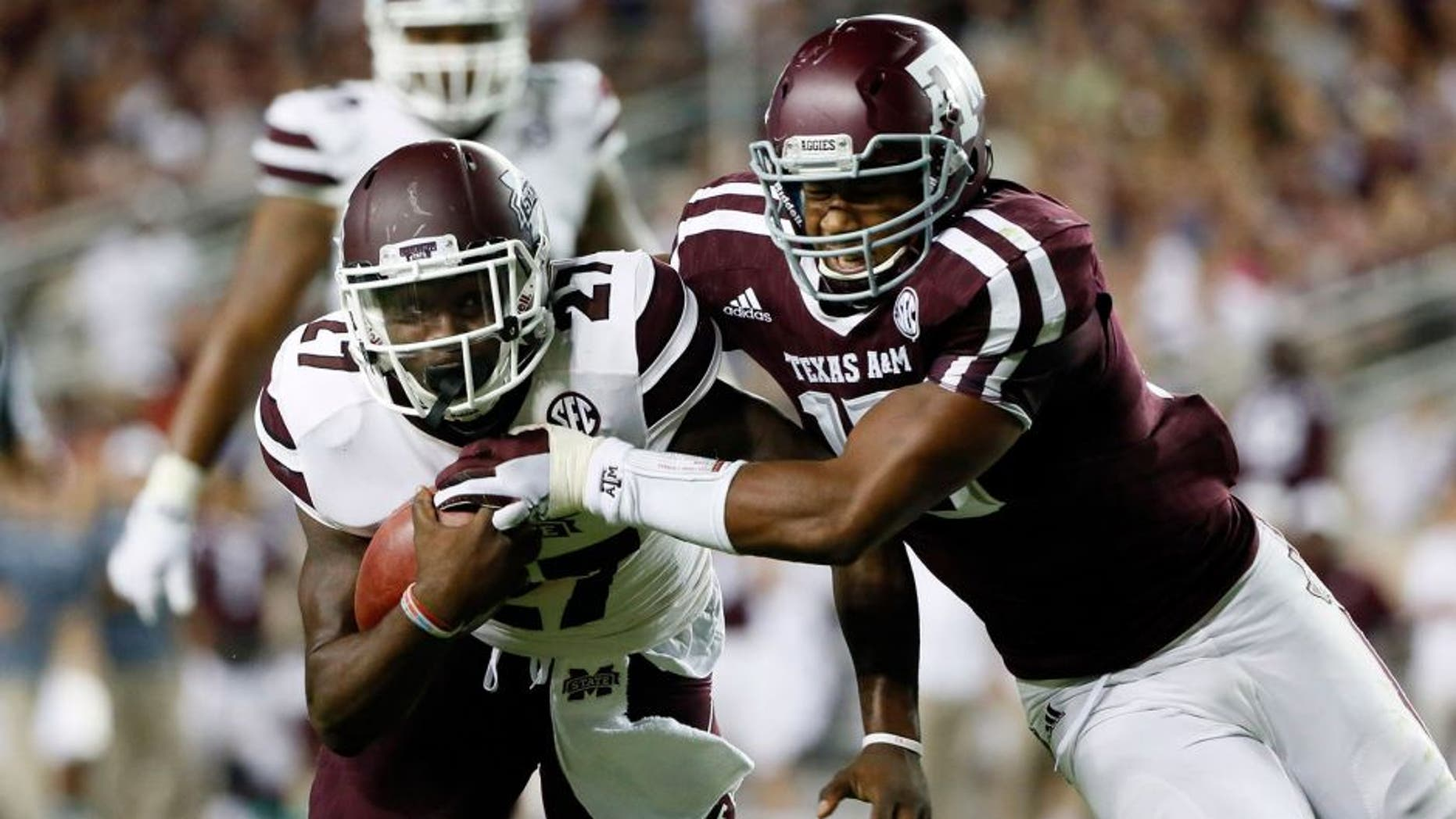 Oct 3, 2015; College Station, TX, USA; Mississippi State Bulldogs running back Aeris Williams (27) carries the ball as Texas A&M Aggies defensive lineman Myles Garrett (right) defends during the second half at Kyle Field. Texas A&M won 30-17. Mandatory Credit: Soobum Im-USA TODAY Sports
