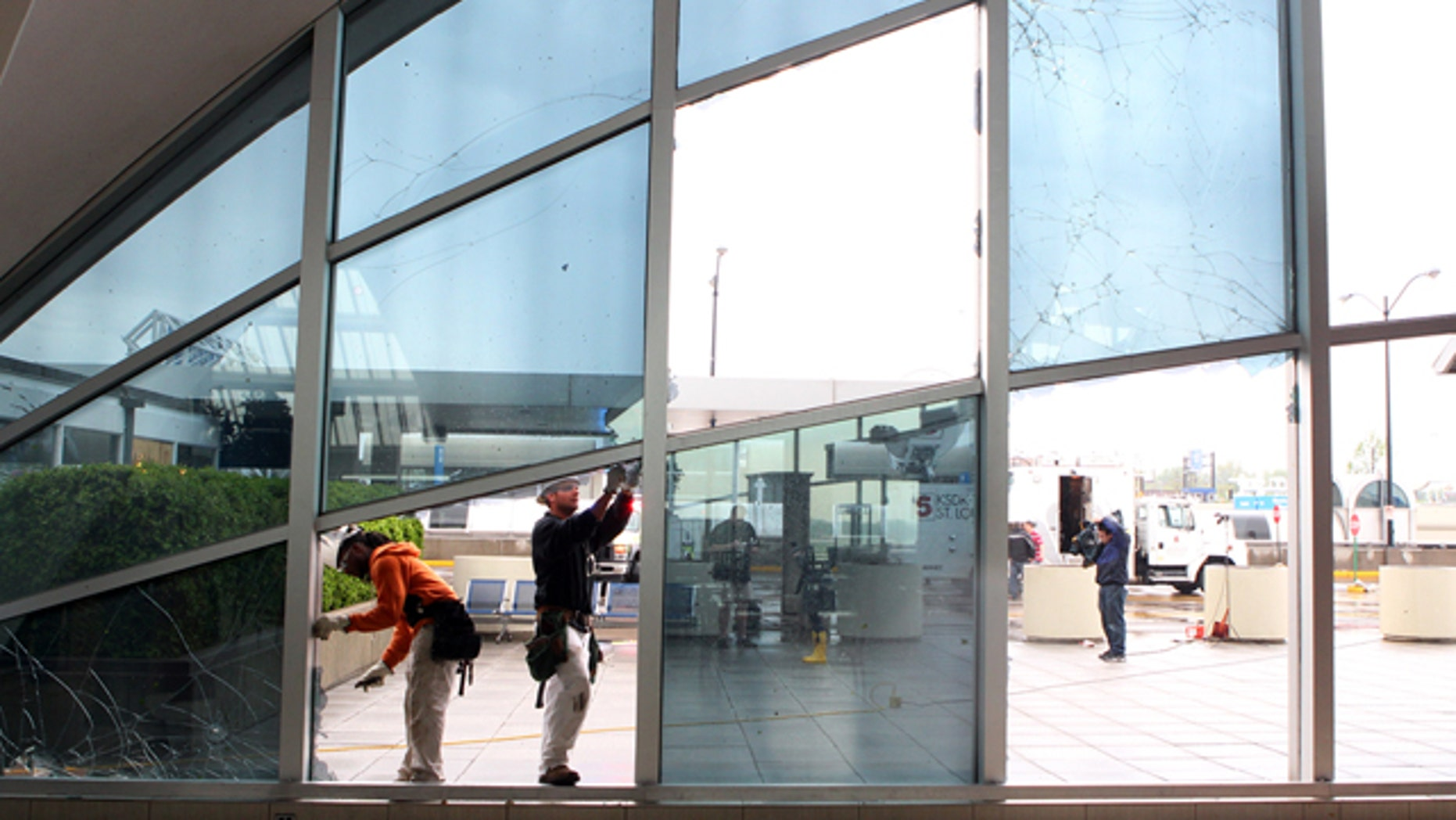 April 23: From left to right, Shaun Jones and Jacob Caldwell of BAM Contracting in St. Louis, work to repair damage to windows in the main terminal of St. Louis' Lambert International Airport
