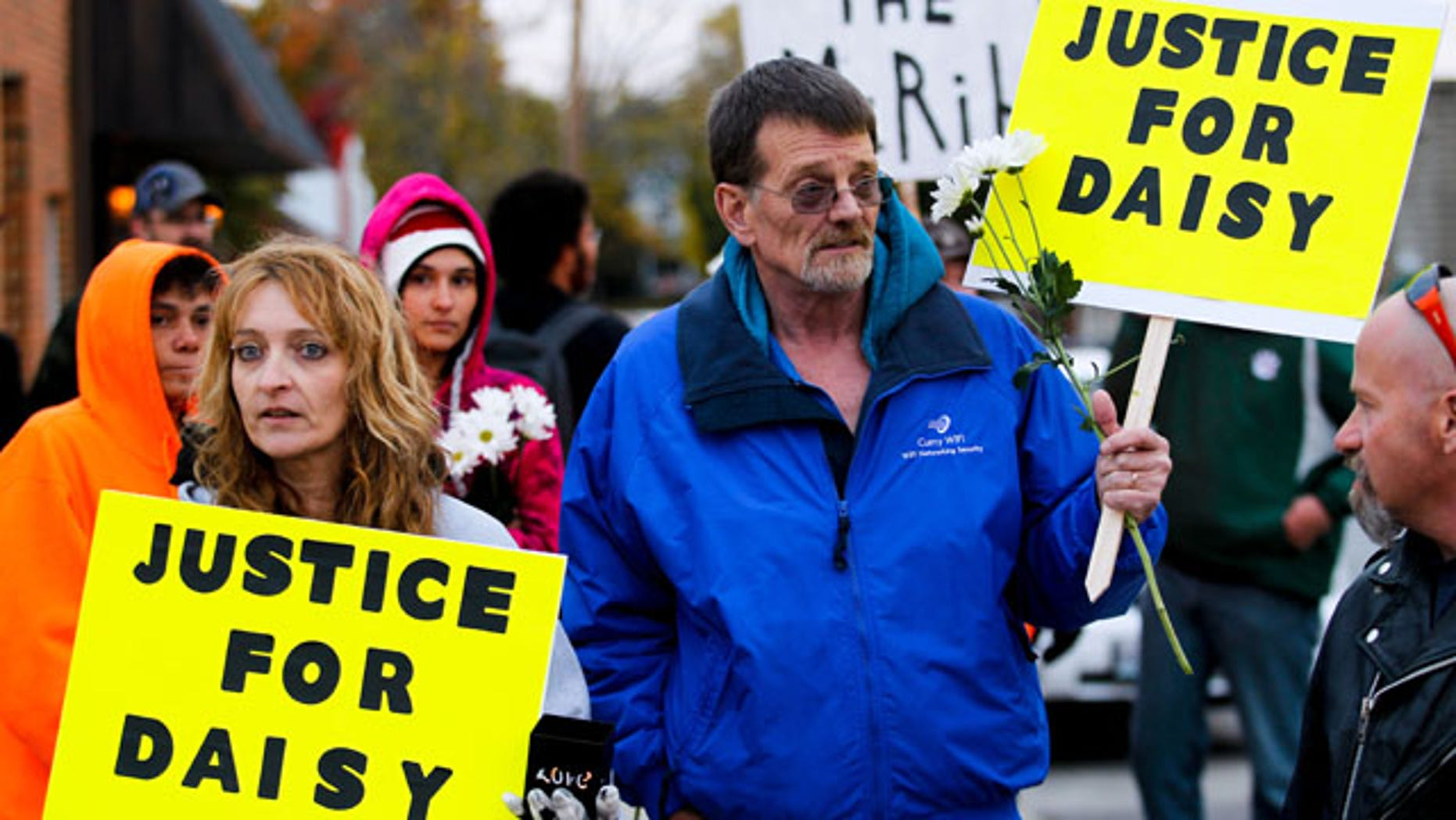 """October 22, 2013: Shana Curry, left, and her husband Scott Curry hold signs at the """"Justice for Daisy"""" rally in Maryville, Mo. The rally was organized on the Internet on behalf of Daisy Coleman, a girl who says she was sexually assaulted nearly two years ago when she was 14. (AP Photo/The St. Joseph News-Press, Sait Serkan Gurbuz)"""