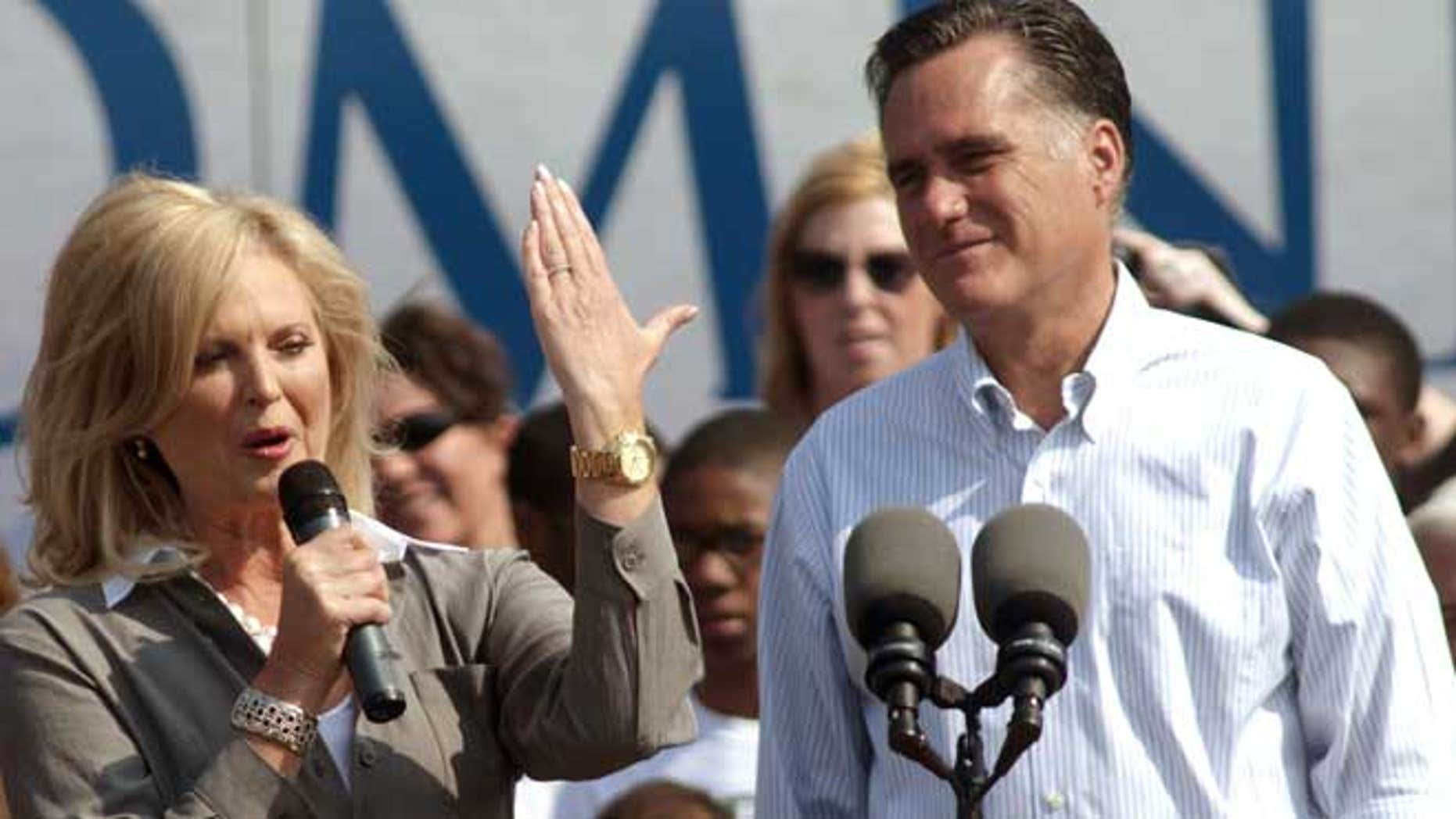 """June 19, 2012: Ann Romney uses her hand as a Michigan """"map"""" while making a speech as her husband, Republican presidential candidate, former Massachusetts Gov. Mitt Romney, right, listens during a campaign stop at Bavarian Inn Lodge in Frankenmuth, Mich."""