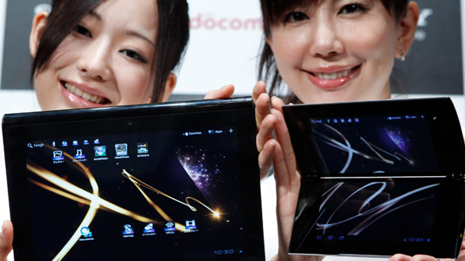 Sept. 1, 2011: Models show off Sony's new tablet computers, Tablet S, left, and Tablet P during a launch event in Tokyo. The wedge-shaped Tablet S, about the size of an iPad, can double as a universal remote control while the Tablet P opens like a book to reveal two screens.