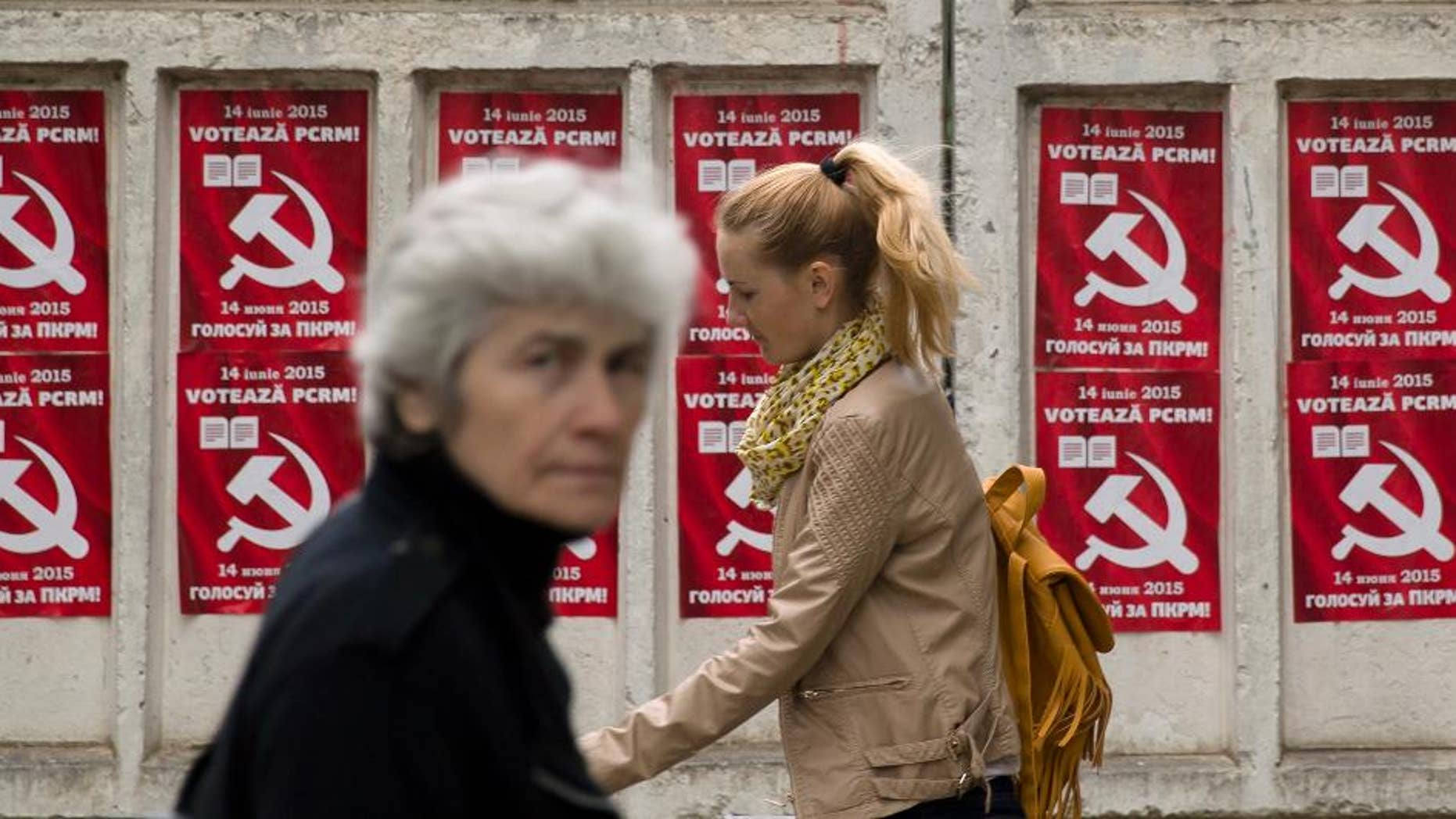 FILE - In this May 28, 2015, file photo, people walk by posters advertising the Party of Communists of Moldova, in Chisinau, Moldova. Moldovans are voting in local elections Sunday, June 14, 2015, which are seen as a test of whether the country is committed to European integration or will move closer to Russia's orbit. (AP Photo/Vadim Ghirda, File)